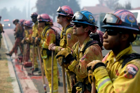 Fire crews line up as they watch a wildfire on a ridge top while protecting a residential area from the Holy Fire on Friday in Lake Elsinore.