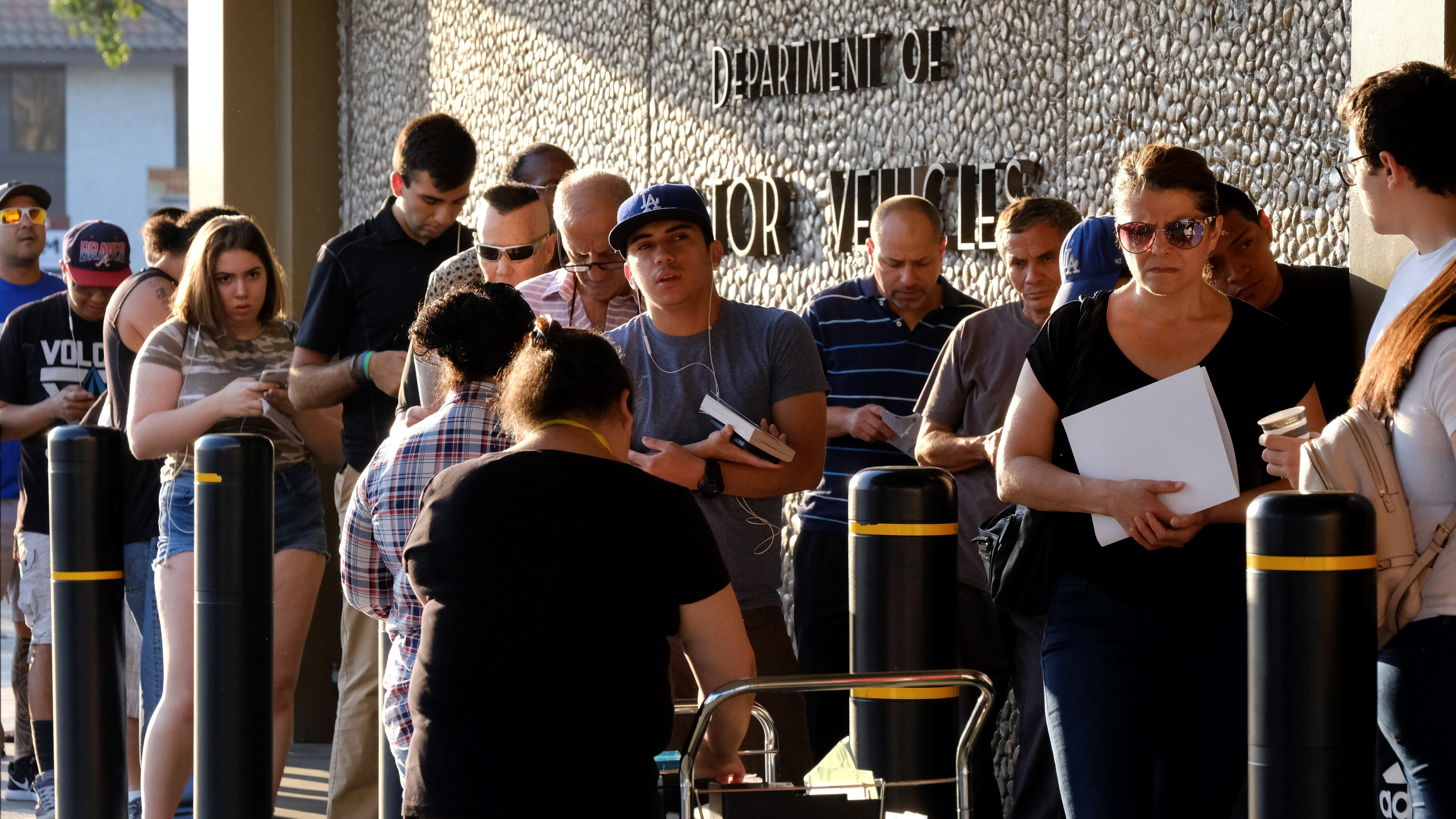 """People line up outside a California Department of Motor Vehicles office prior to opening in Van Nuys on Tuesday. The DMV blames long wait times at its offices on underestimations of the time it takes to process """"Real ID"""" applicants."""