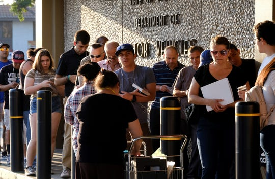 People line up outside a California Department of Motor Vehicles office prior to opening in Van Nuys in this file photo.
