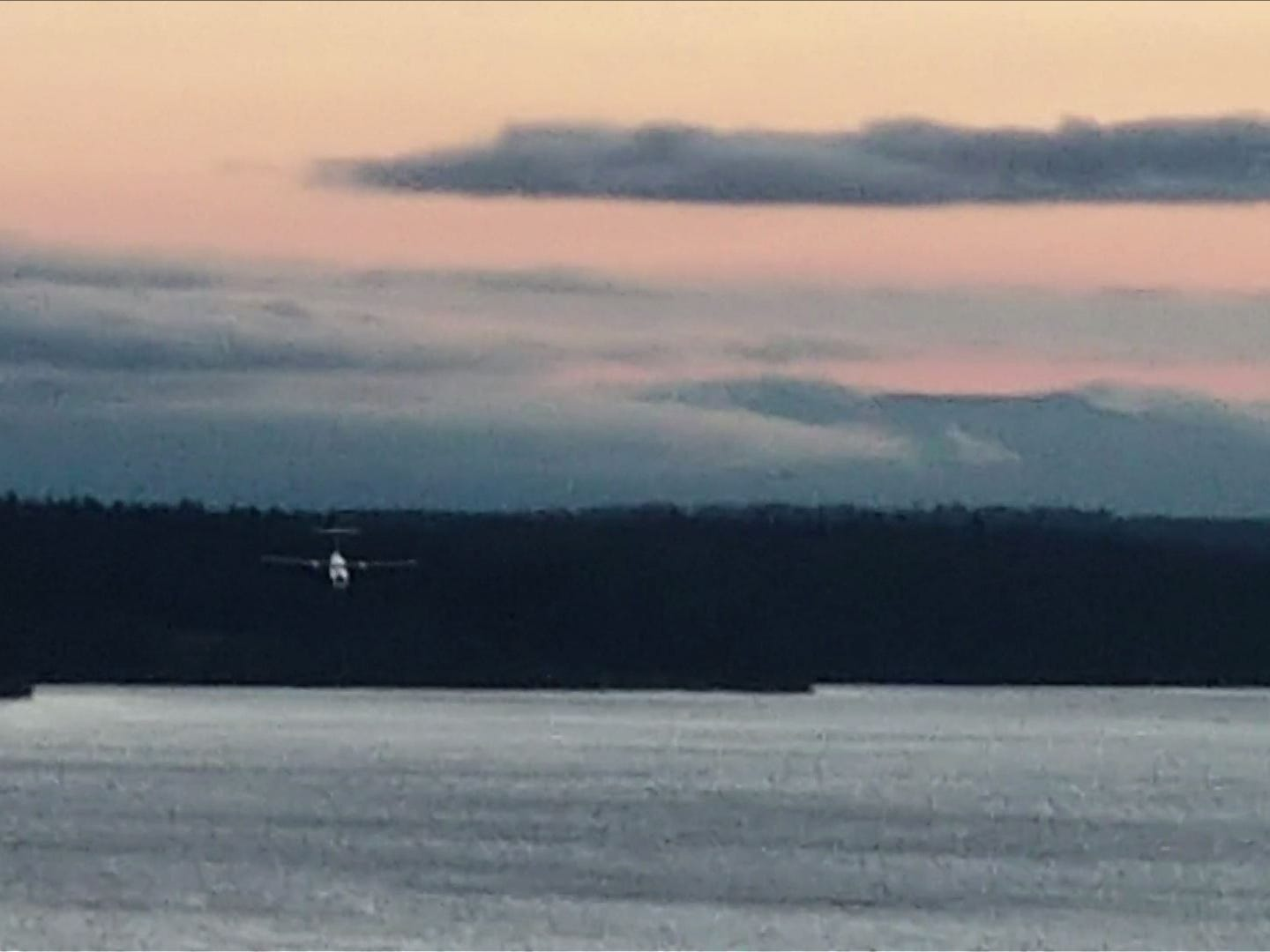 """This frame grab taken from footage filmed by bystander John Wauldron on August 10, 2018 with his Galaxy S8 at Chambers Bay Park and Golf Course in University Place Washington, shows an empty passenger airplane, stolen from the Seattle-Tacoma airport, making an unlikely upside-down aerial loop, then flying low over Puget Sound before crashing into the sparsely populated Ketron Island in the northwestern US state of Washington. - An apparently suicidal mechanic stole an empty passenger plane from the Seattle-Tacoma airport late August 10, 2018, took it for a brief flight then crashed it in an incident officials said was unrelated to terrorism. Two military F-15s were scrambled to chase the stolen plane, but local officials said the jets """"were not involved in the crash."""" Video taken by a bystander John Wauldron, showed the passenger airplane making an unlikely upside-down aerial loop, then flying low over Puget Sound before crashing into the sparsely populated Ketron Island in the northwestern US state of Washington. (Photo by Handout / John Wauldron / AFP) / RESTRICTED TO EDITORIAL USE - MANDATORY CREDIT """"AFP PHOTO / John WAULDRON """" - NO MARKETING NO ADVERTISING CAMPAIGNS - DISTRIBUTED AS A SERVICE TO CLIENTS ---HANDOUT/AFP/Getty Images ORIG FILE ID: AFP_18A8DE"""