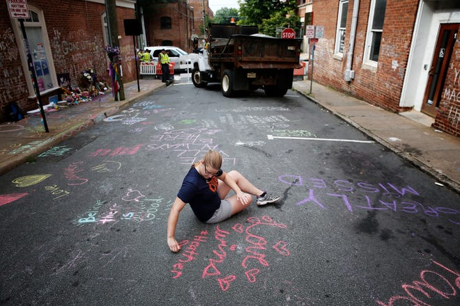 Kim Ganczak writes on the street with chalk near a makeshift memorial for Heather Heyer, who was killed one year ago tomorrow during a deadly clash, August 11, 2018 in Charlottesville, Virginia.