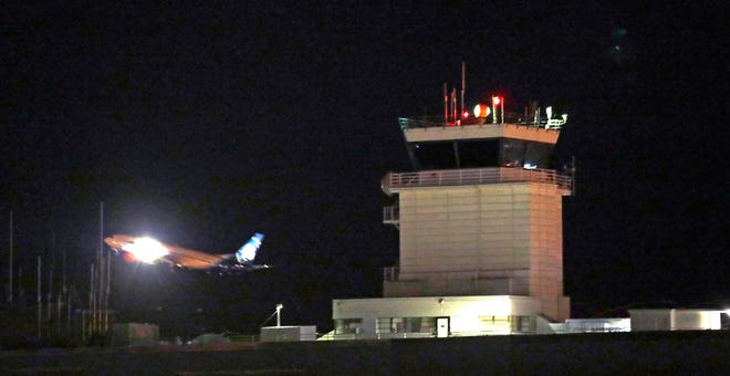 A plane flies past a control tower at Sea-Tac International Airport Friday in Washington. An airline mechanic stole an Alaska Airlines plane without any passengers and took off from Sea-Tac International Airport Friday night before crashing near Ketron Island, officials said.