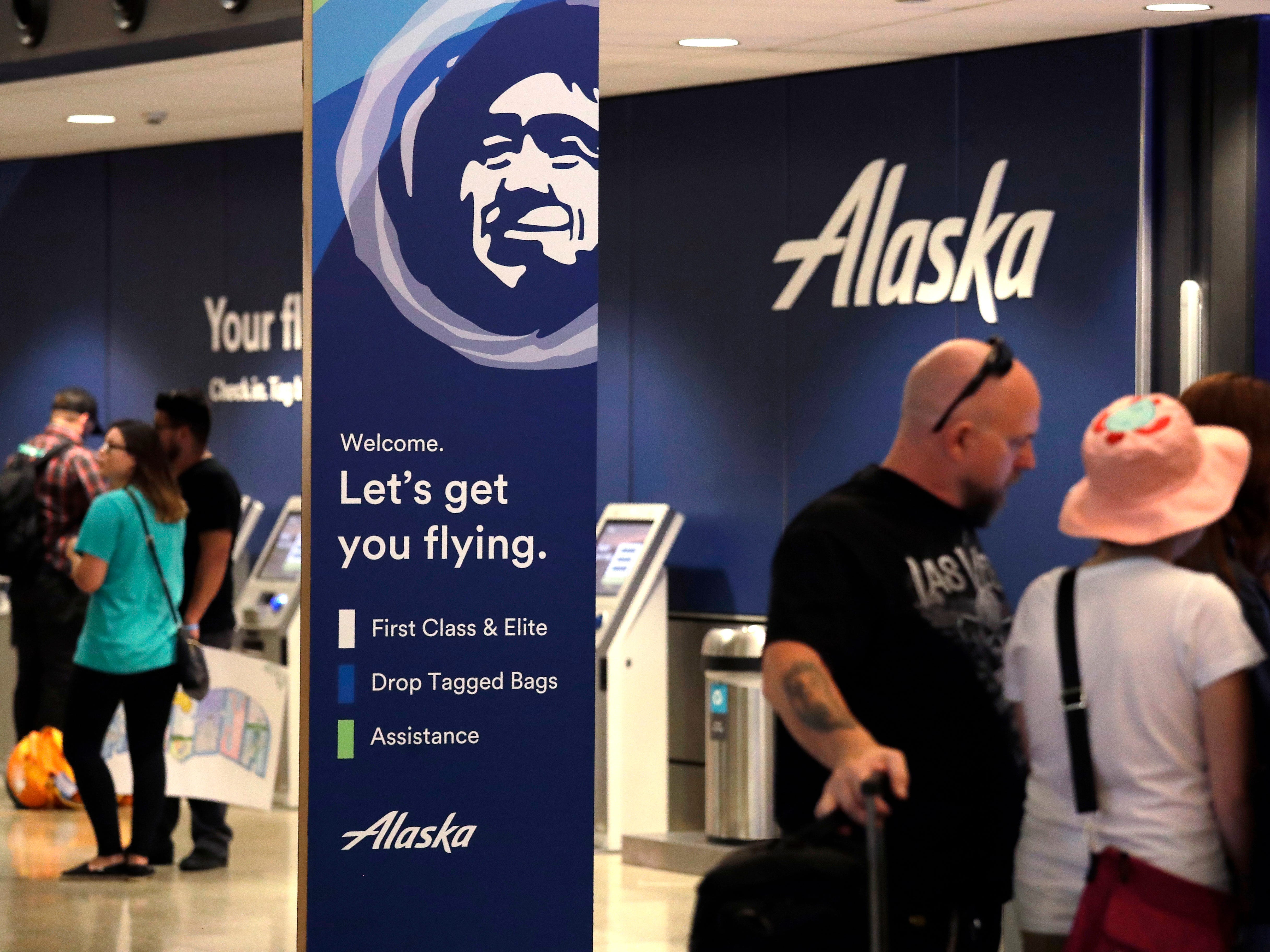 People stand in the Alaska Airlines ticket area at Sea-Tac International Airport Friday, Aug. 10, 2018, in SeaTac, Wash.An airline mechanic stole an Alaska Airlines plane without any passengers and took off from Sea-Tac International Airport in Washington state on Friday night before crashing near Ketron Island, officials said. (AP Photo/Elaine Thompson) ORG XMIT: WAET114