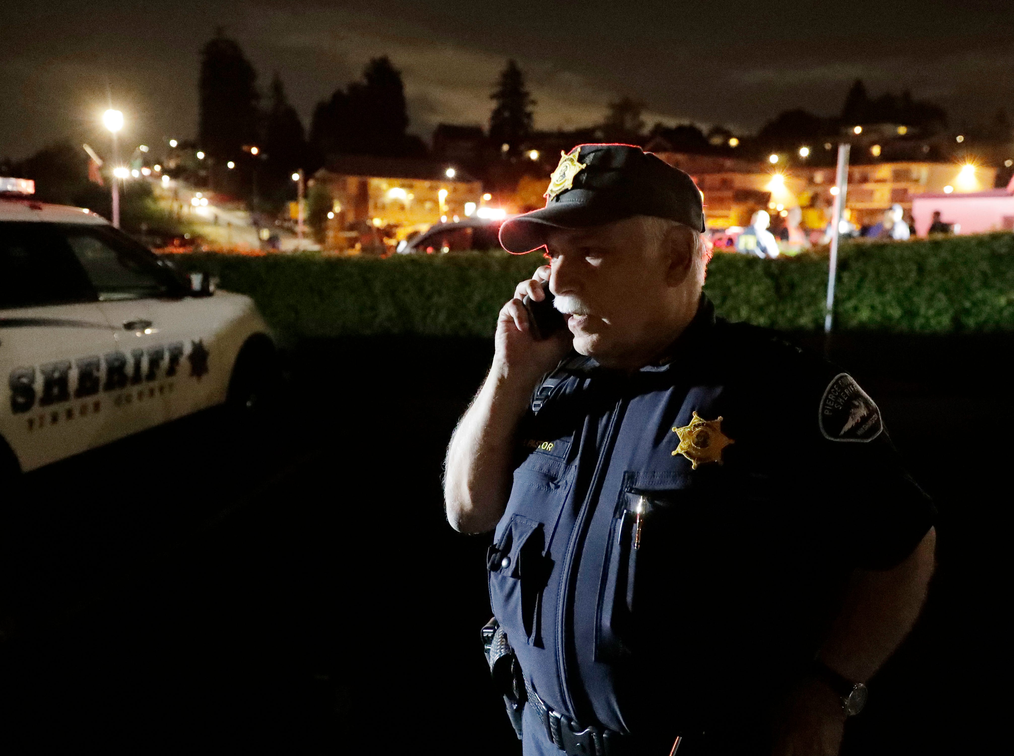 Pierce County Sheriff Paul Pastor talks on his phone at a staging area, Friday, Aug. 10, 2018, at the ferry terminal in Steilacoom, Wash., near where a Coast Guard spokeswoman said the agency was responding to a report of a smoke plume and possible plane crash. Earlier in the evening, officials at Seattle-Tacoma International Airport said an Alaska Airlines plane had been stolen and later crashed.