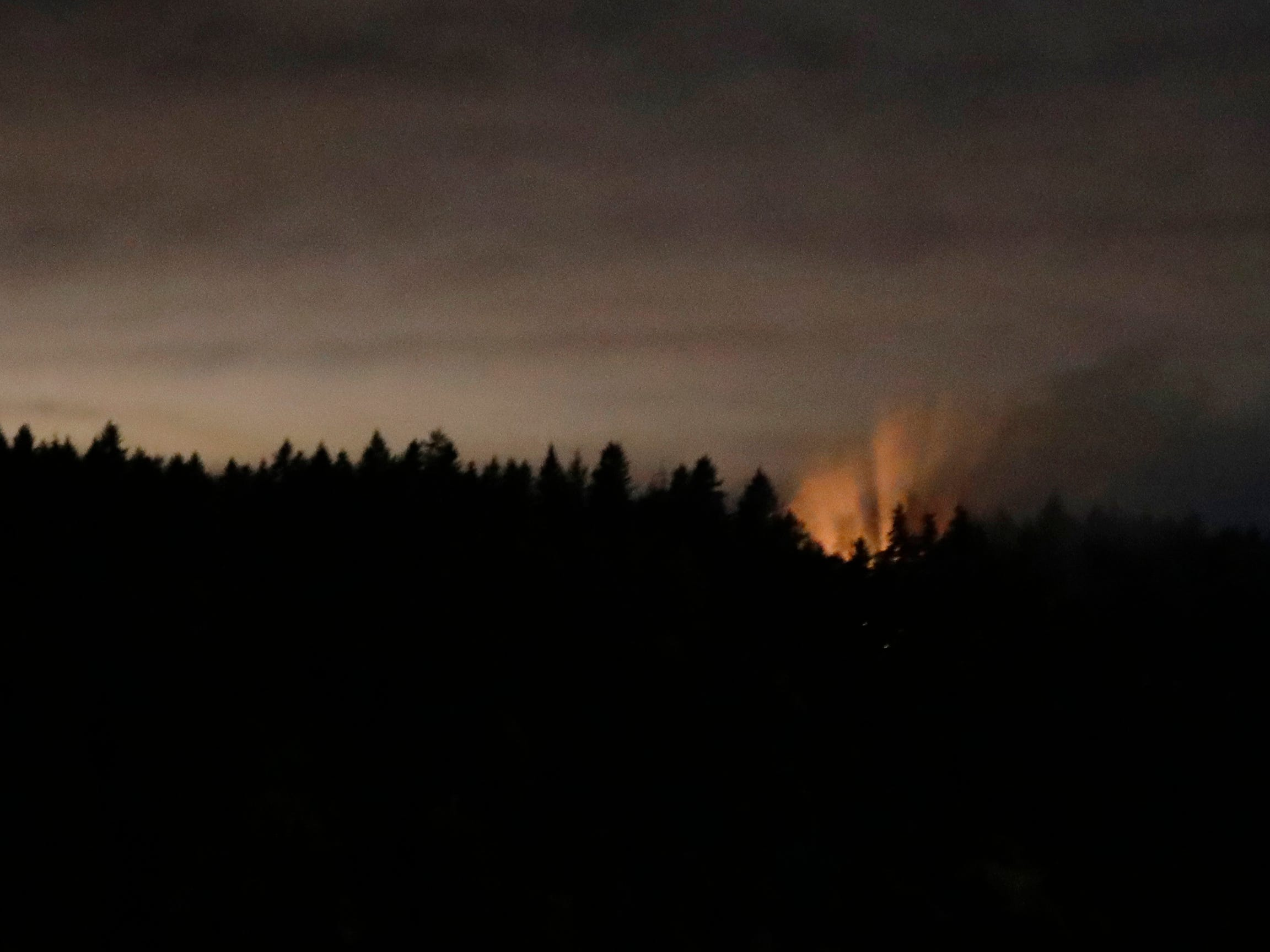In this long-exposure photo, smoke and an orange glow are seen on Ketron Island in Washington state, early Saturday, Aug. 11, 2018 as viewed from near Steilacoom, Wash. On Friday, an airline mechanic stole an empty Horizon Air turboprop plane, took off from Seattle-Tacoma International Airport and was chased by military jets before crashing onto Ketron, a small island in the Puget Sound, on Friday night, officials said.