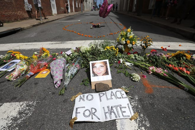 Flowers surround a photo of 32-year-old Heather Heyer, Aug. 13, 2017, Charlottesville, Va.