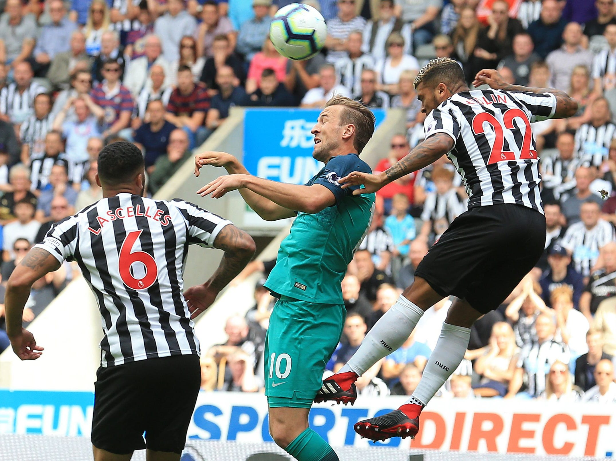Tottenham's Harry Kane goes up for the ball against Newcastle United's Jamaal Lascelles and DeAndre Yedlin.