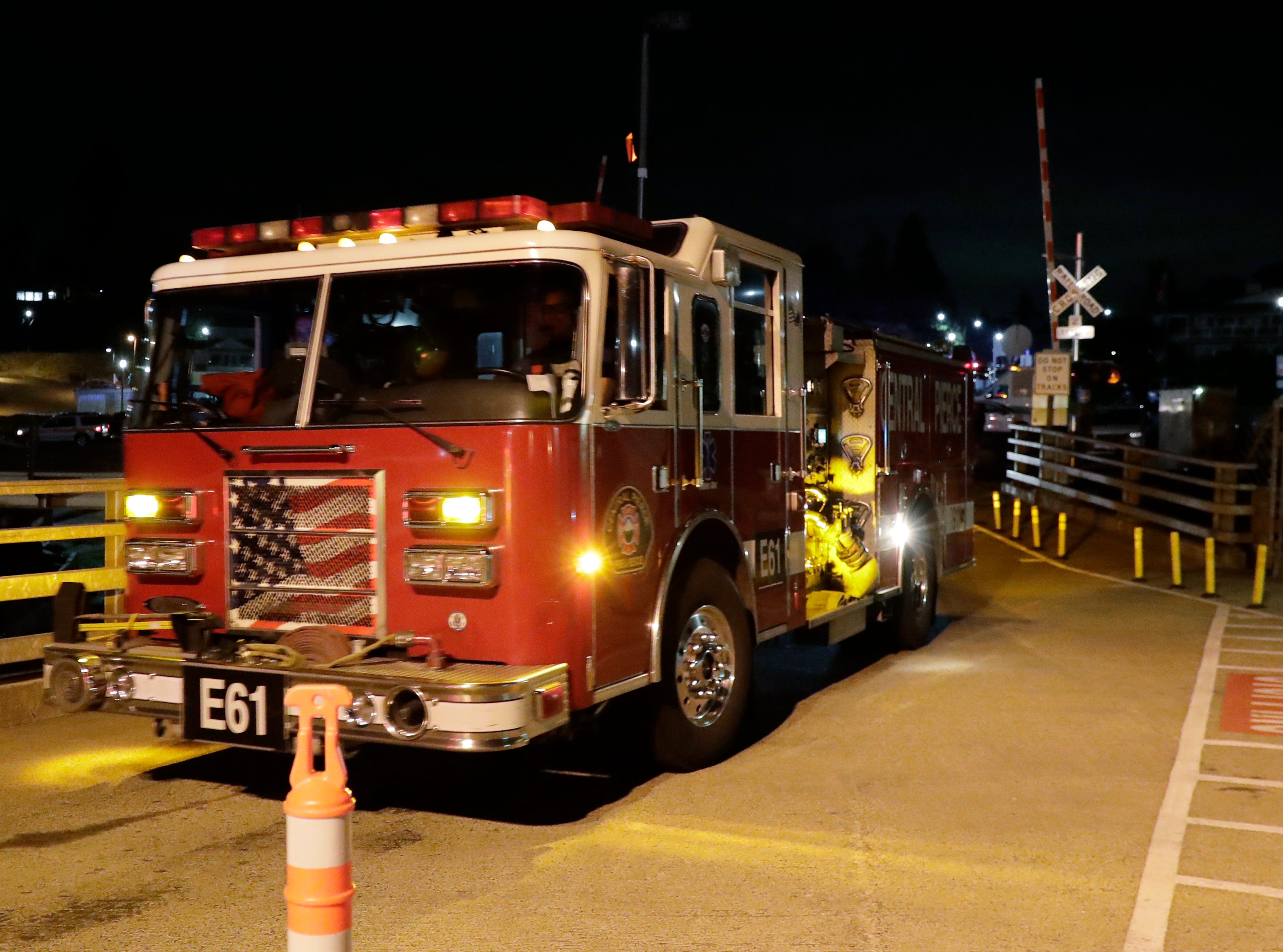 Fire trucks drive toward a ferry boat headed to Ketron Island, Friday, Aug. 10, 2018, at the ferry terminal in Steilacoom, Wash.