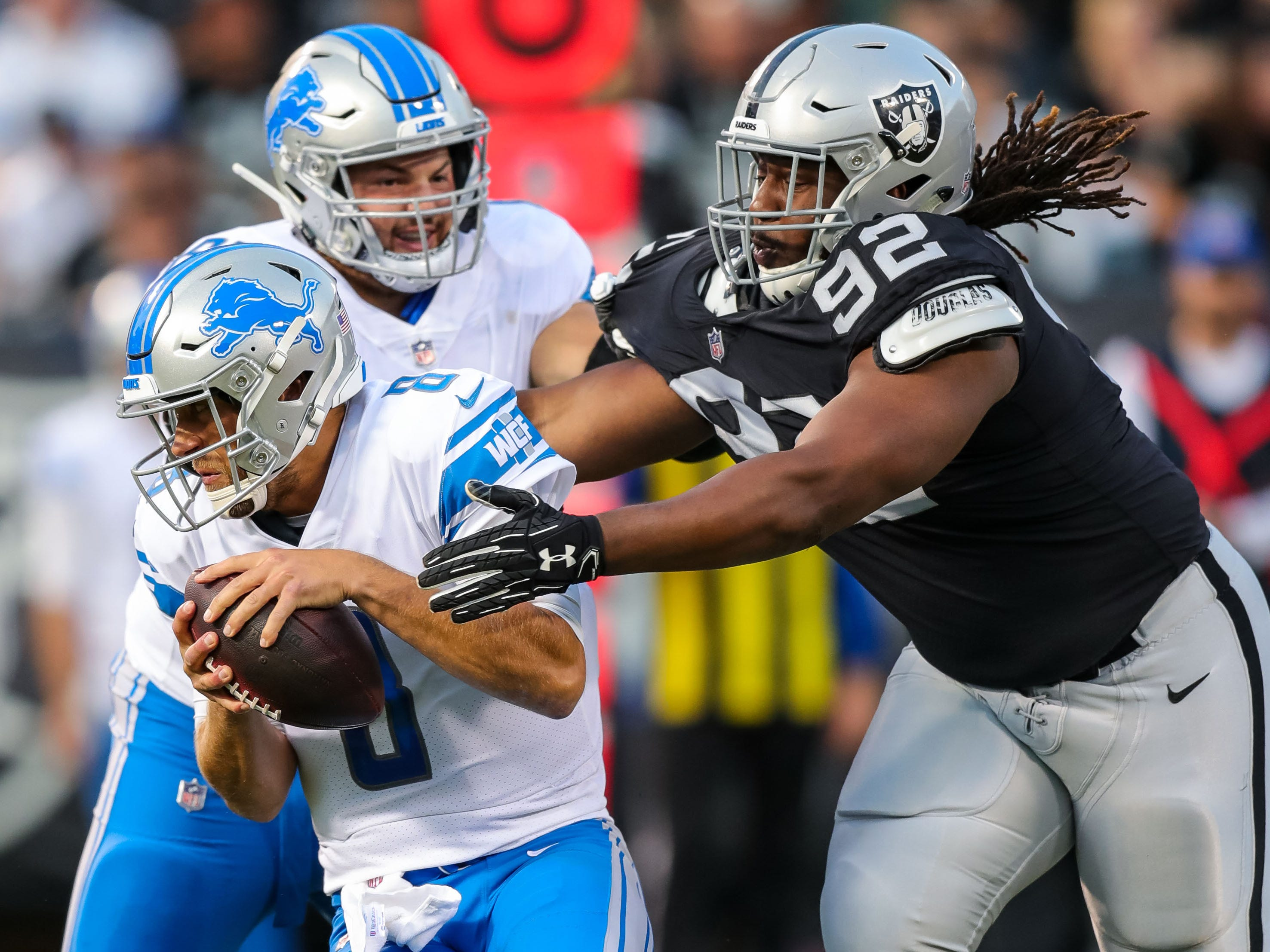 Detroit Lions quarterback Matt Cassel is sacked by Oakland Raiders nose tackle P.J. Hall during the first quarter at Oakland Coliseum.