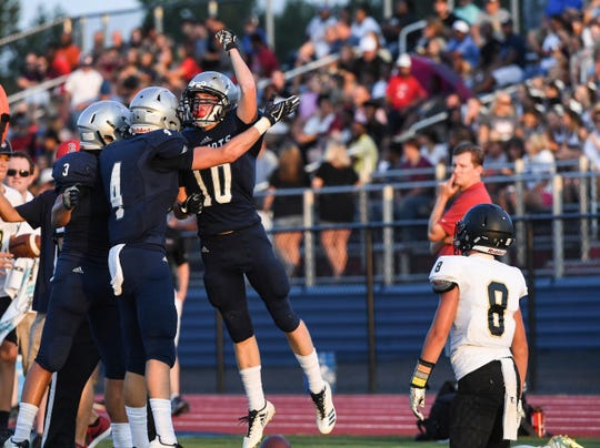 Powdersville Caden Beck celebrates a turnover with teammates near TL Hanna senior Peyton Newell during the second game of the 2018 Anderson County FCA Jamboree at Belton-Honea Path High School in Honea Path on Friday, August 10.