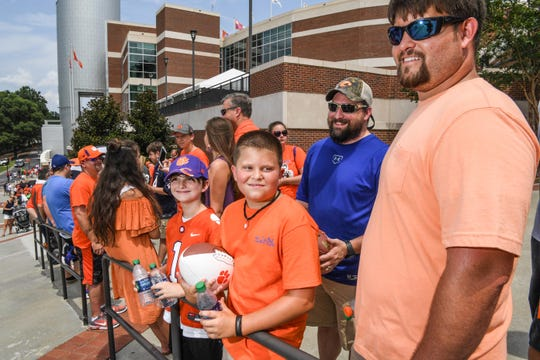 Brody Crump, middle, and his father Andrew Crump, right, of Toccoa, Georgia, stand with Brantley Addison, left, and his father Jason Addison (in blue) waiting to see quarterbacks for the Clemson University football fan day in Memorial Stadium on Sunday, August 12, 2018.
