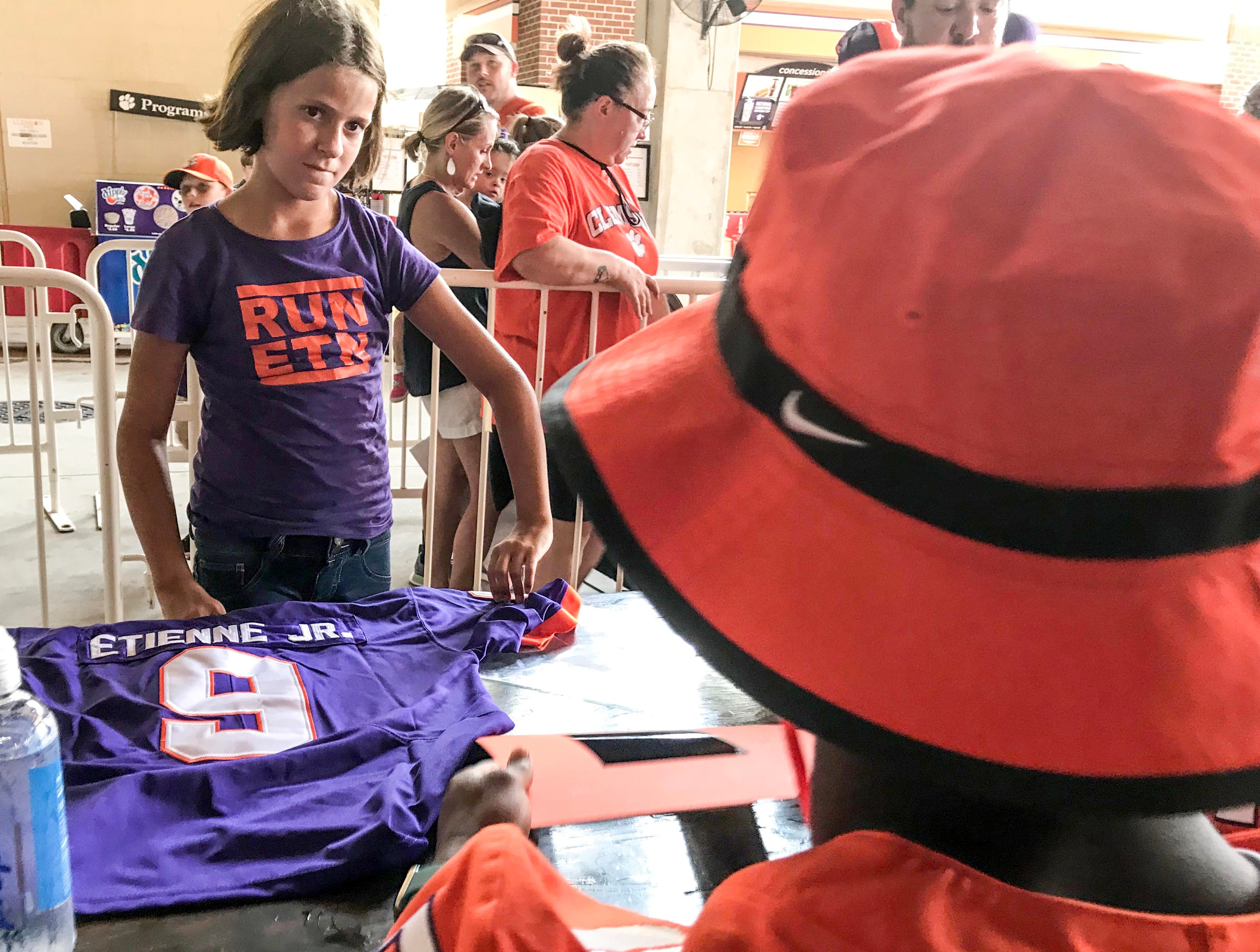 Meredith Thompson, left, 11, of Conway meets her favorite player Travis Etienne at the Clemson University football fan day in Memorial Stadium on Sunday, August 12, 2018.