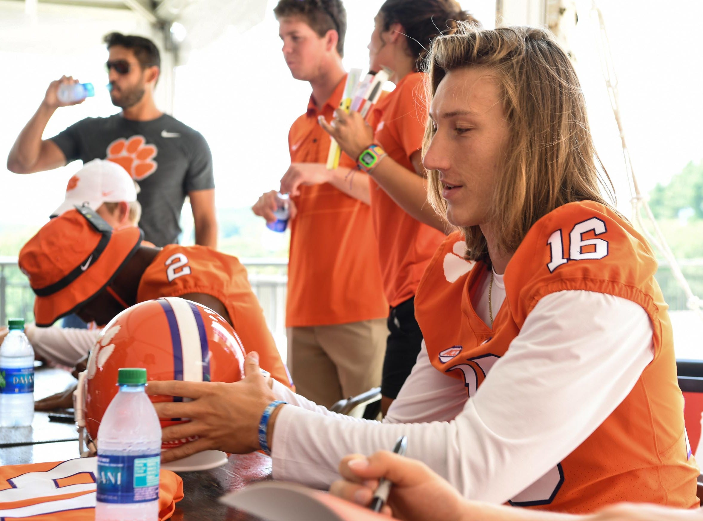 Clemson quarterback Trevor Lawrence (16) signs autographs during Clemson University football fan day in Memorial Stadium on Sunday, August 12, 2018.