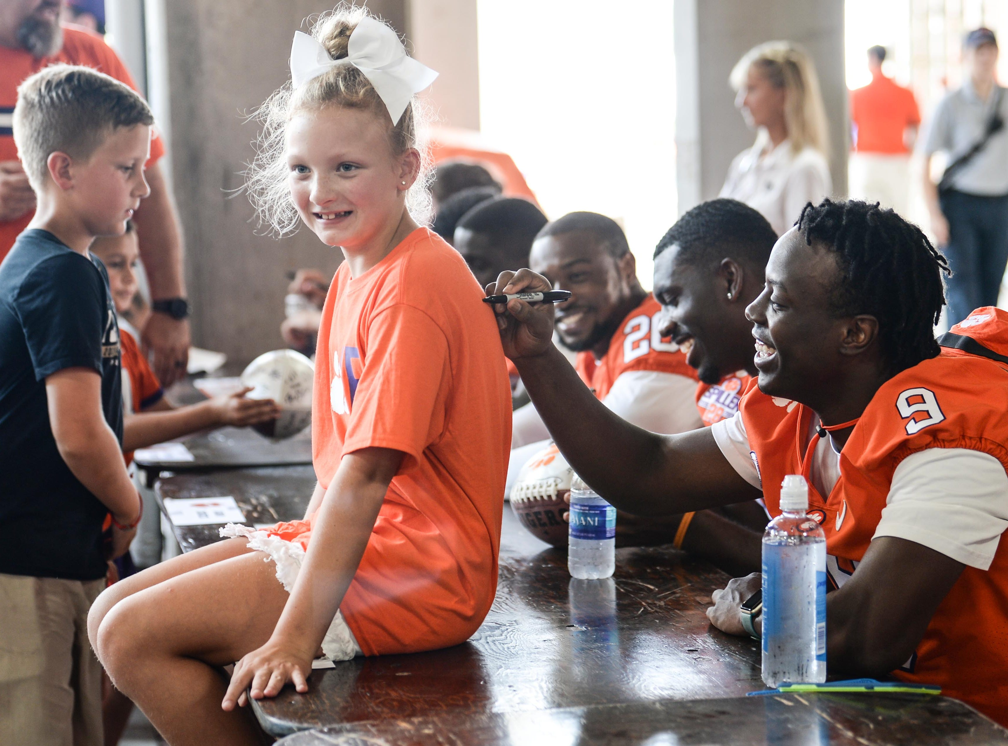 Olivia Wilson of Aiken gets her t-shirt signed by Clemson running back Travis Etienne (9) during Clemson University football fan day in Memorial Stadium on Sunday, August 12, 2018.