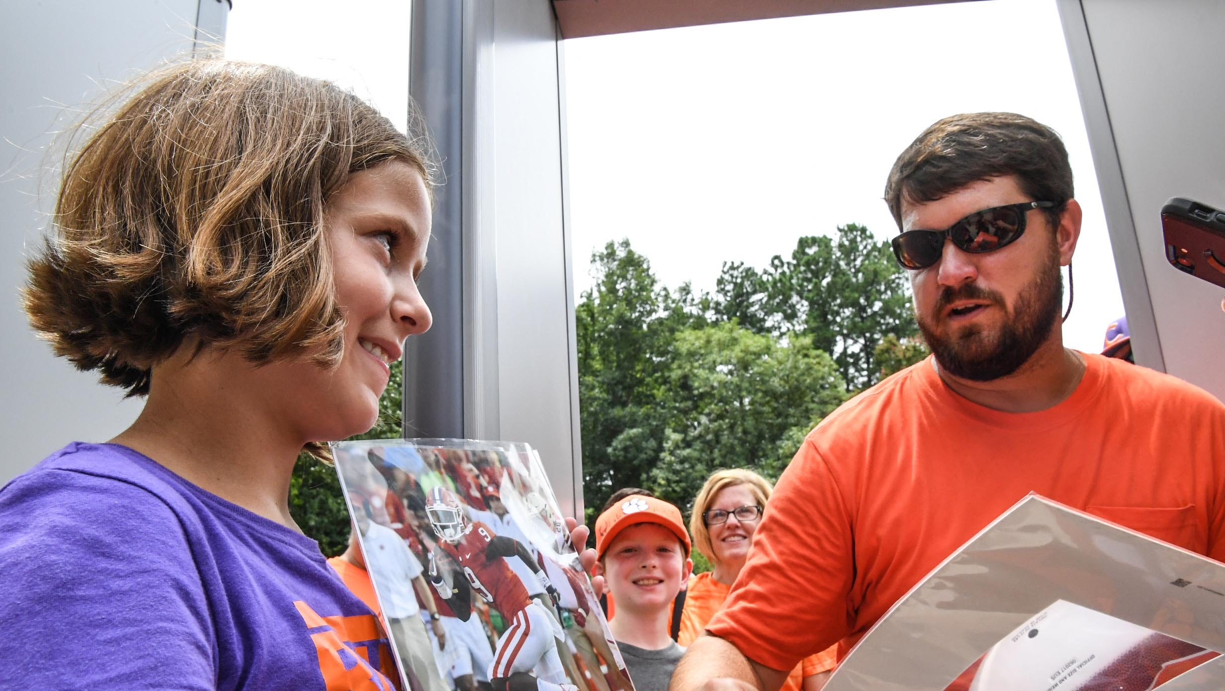 Meredith Thompson, left, 11, of Conway holds a photo of Travis Etienne near her father Michael Thompson, waiting to see players at the Clemson University football fan day in Memorial Stadium on Sunday, August 12, 2018.