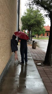 A couple talking a rainy afternoon walk downtown takes a smoke break. Rain is forecast for Abilene into Monday.
