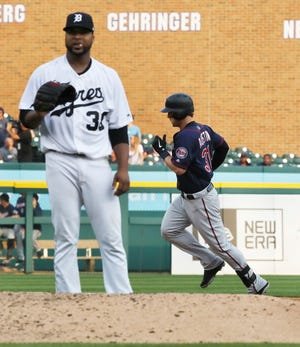 Minnesota Twins designated hitter Tyler Austin, right, rounds the bases as Detroit Tigers starting pitcher Francisco Liriano stands behind the mound after giving up a two-run home run during the fifth inning of a baseball game, Saturday, Aug. 11, 2018, in Detroit.