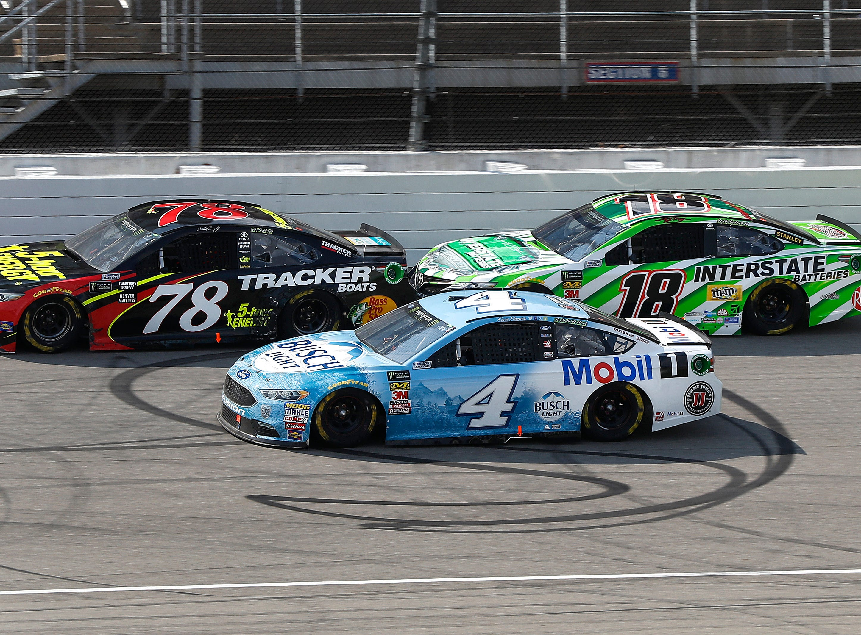 Martin Truex Jr. (78), Kevin Harvick (4) and Kyle Busch (18) race each other for position during a NASCAR Cup Series auto race at Michigan International Speedway in Brooklyn, Mich., Sunday, Aug. 12, 2018.
