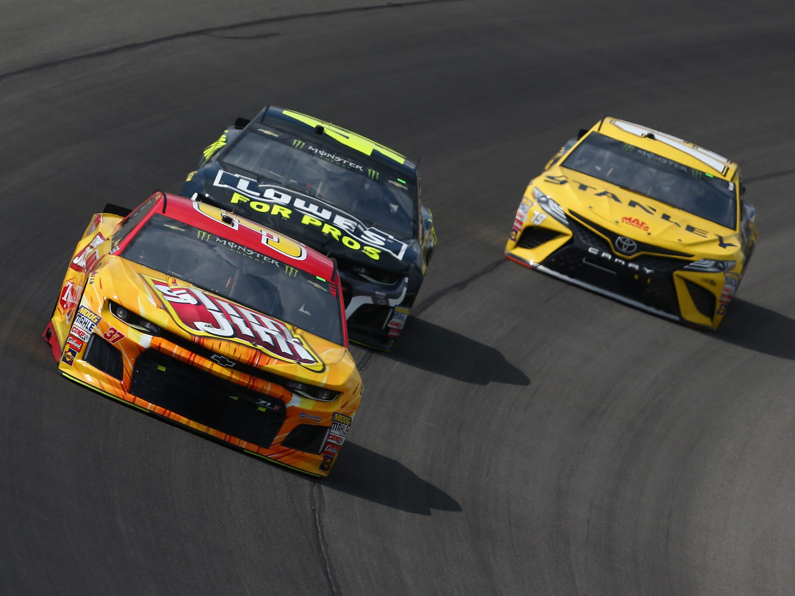 Chris Buescher, driver of the No. 37 Slim Jim Chevrolet, leads Jimmie Johnson, driver of the No. 48 Lowe's for Pros Chevrolet and Daniel Suarez, driver of the No. 19 Stanley Toyota, during the Monster Energy NASCAR Cup Series Consmers Energy 400 at Michigan International Speedway on August 12, 2018 in Brooklyn, Michigan.