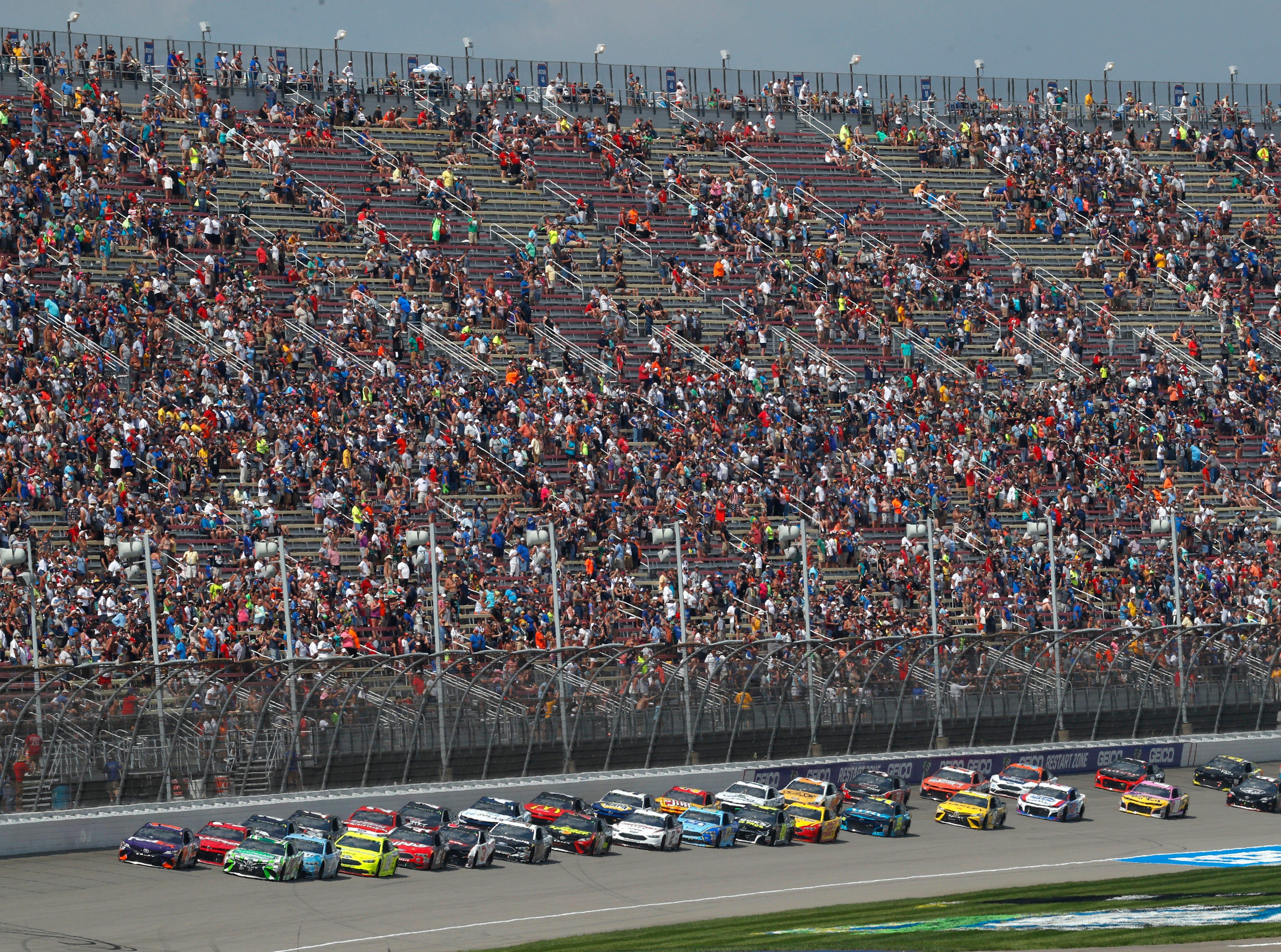 Pole sitter Denny Hamlin leads the field to the start line during a NASCAR Cup Series auto race at Michigan International Speedway in Brooklyn, Mich., Sunday, Aug. 12, 2018. (AP Photo/Paul Sancya)