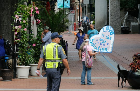 A visitor carries a sign as State Police lock down the downtown area in anticipation of the anniversary of last year's Unite the Right rally in Charlottesville, Va., Saturday, Aug. 11, 2018.