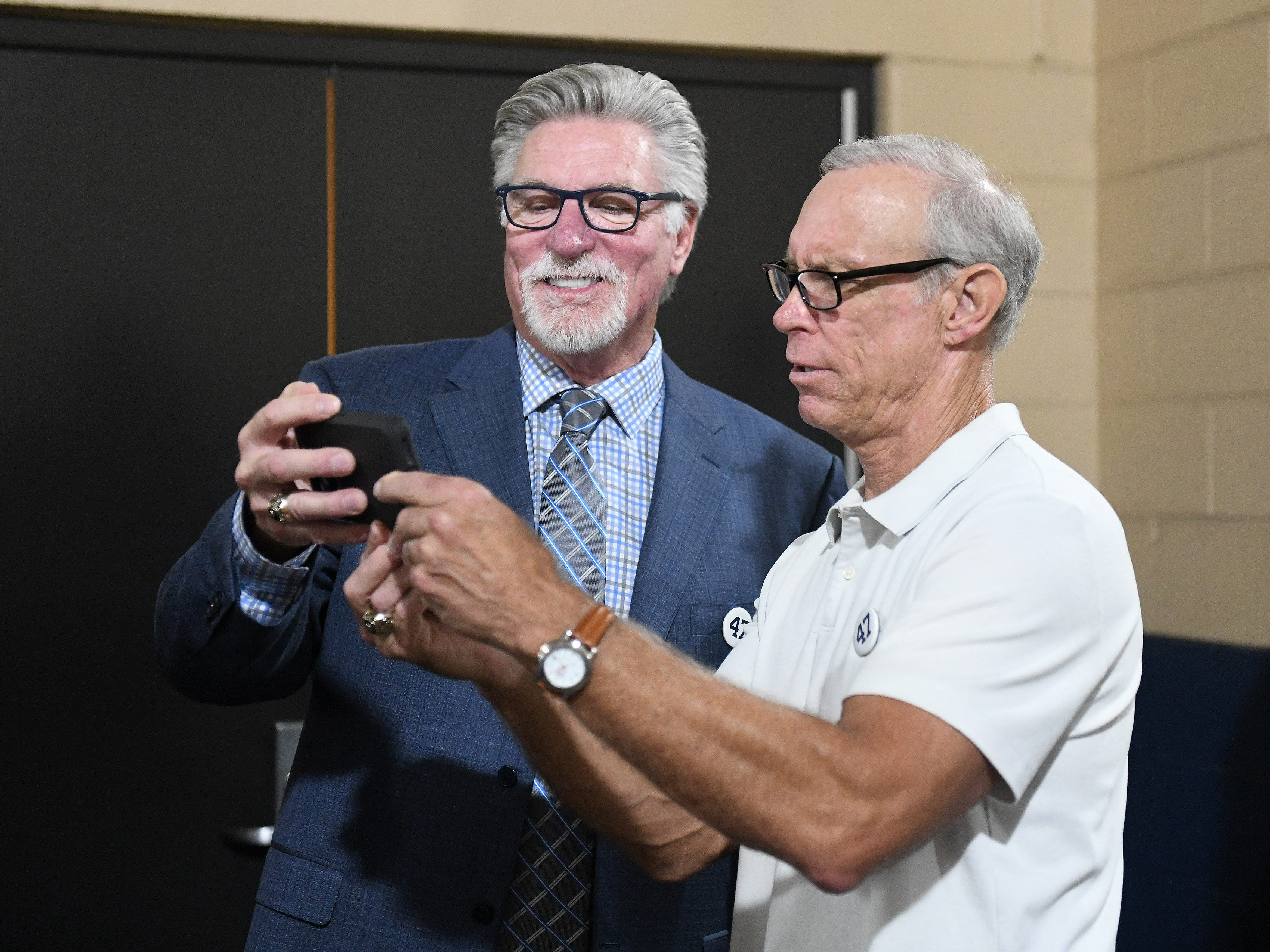Jack Morris, left, and Alan Trammell, both inducted into the Hall of Fame this year, look at something on a phone before the ceremony.