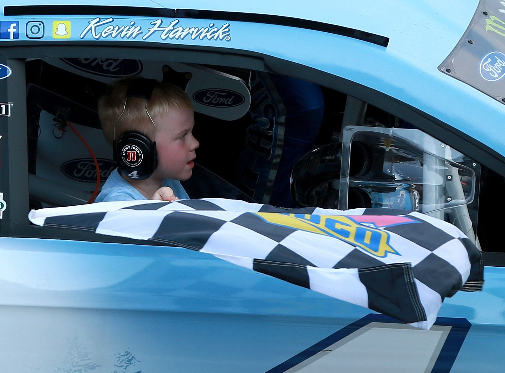 Keelan Harvick, son of Kevin Harvick, driver of the #4 Busch Light/Mobil 1 Ford, celebrates with the checkered flag after his dad won the Monster Energy NASCAR Cup Series Consmers Energy 400 at Michigan International Speedway.