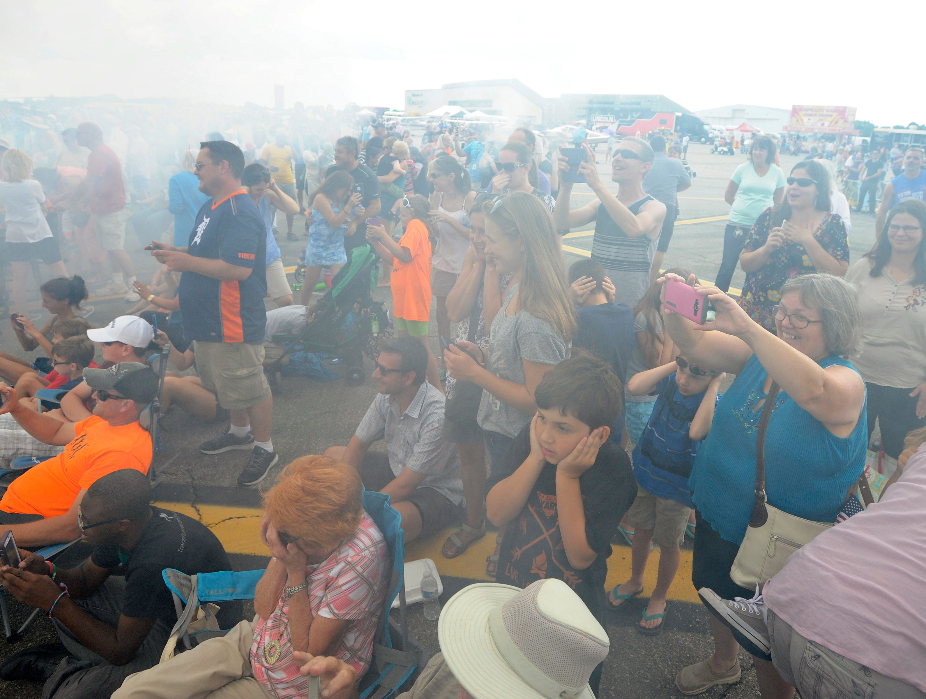 "A wall of smoke made from the spinning wheels of a ""jet truck"" envelops the crowd as they try to take cover or take pictures."