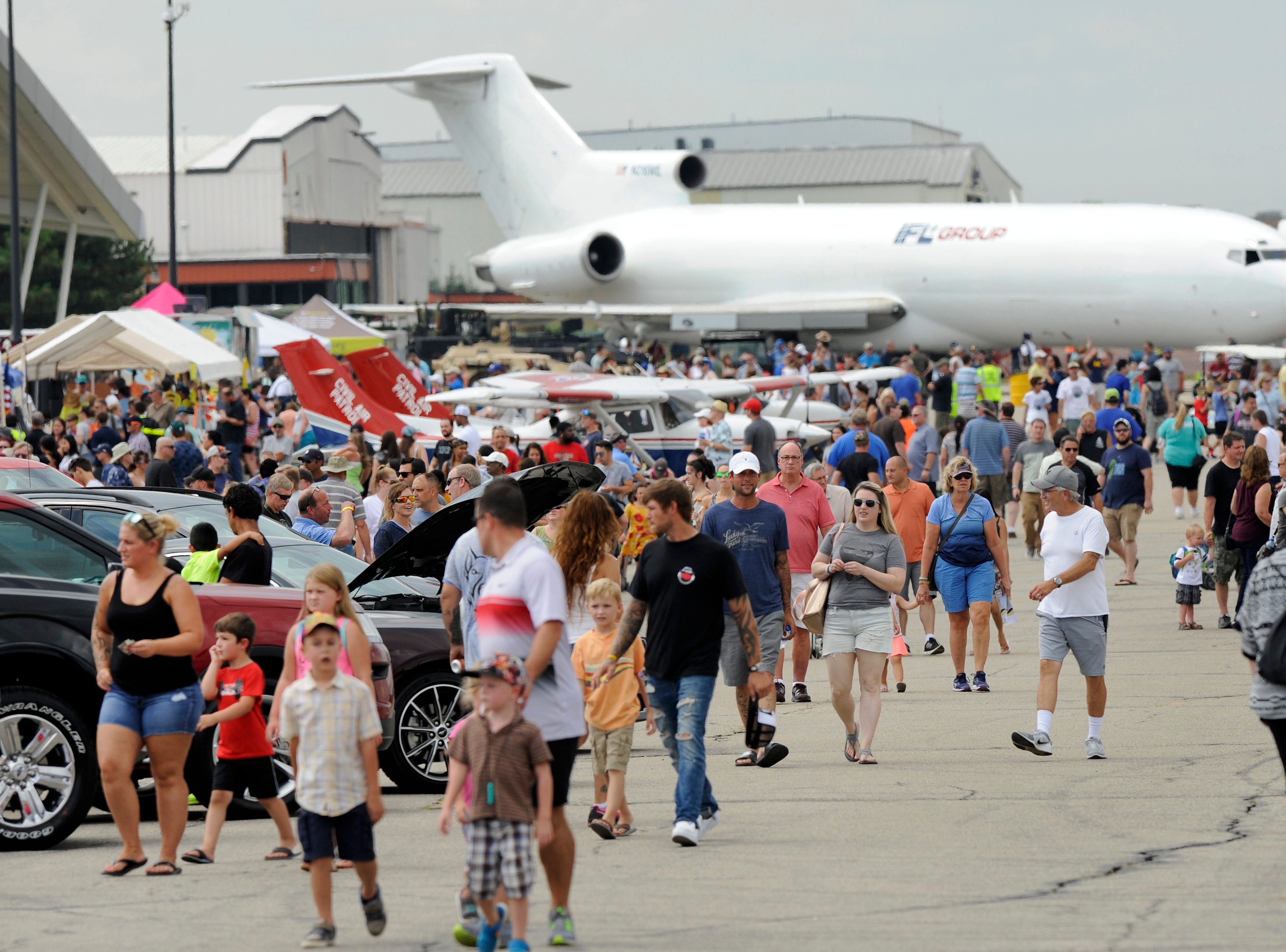 Visitors to the Air Show & Open House look over aircraft, Sunday at the Oakland County International Airport.