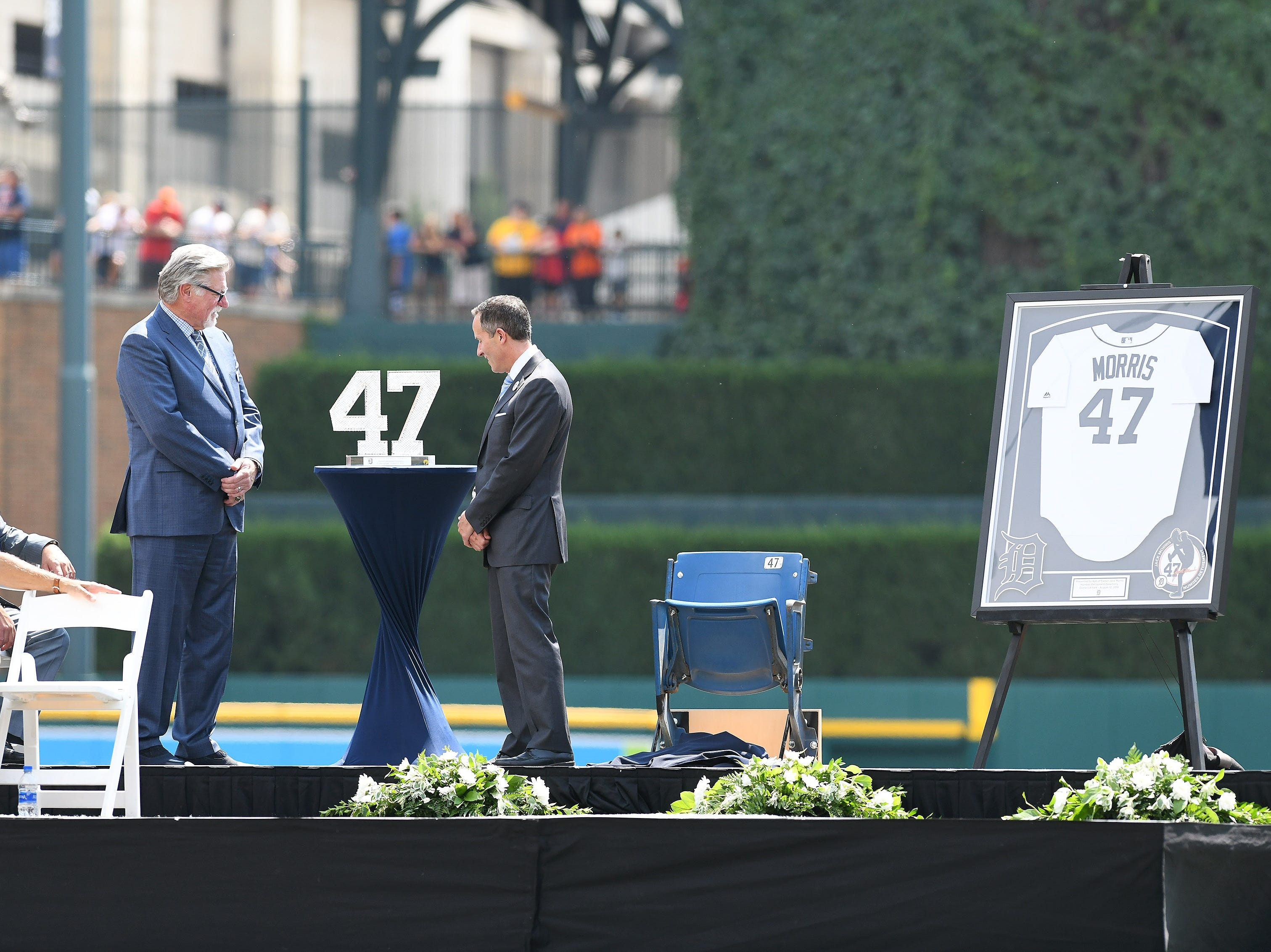 Tigers chairman and CEO Chris Ilitch, center, unveils a Waterford crystal #47 for Jack Morris, left, during the special pregame ceremony.