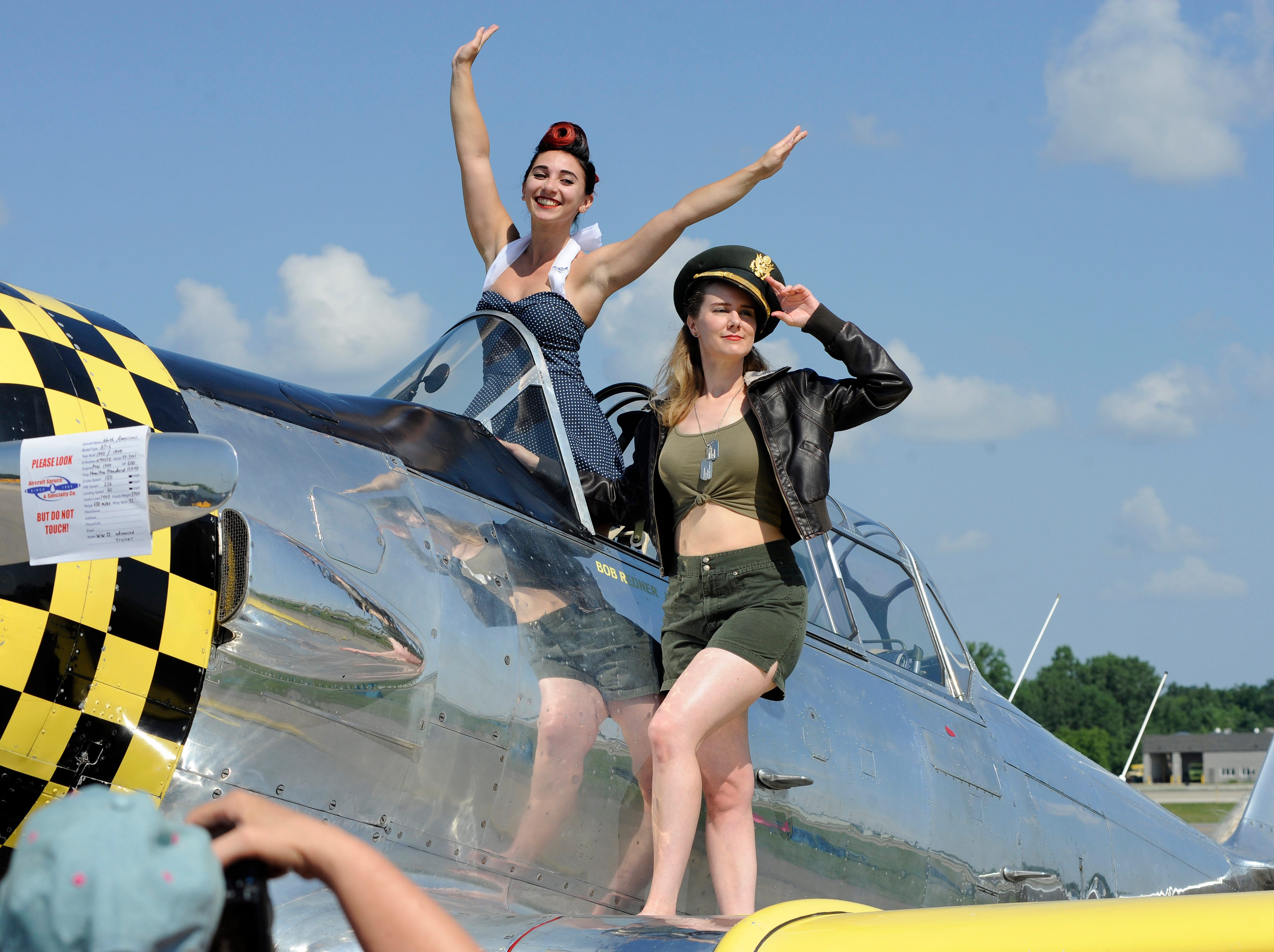 Motor City Belles Jessica Foster, left, and Emily Miller, dressed in historical clothing, pose for photos atop an AT-6 plane, which was a World War II advanced trainer.