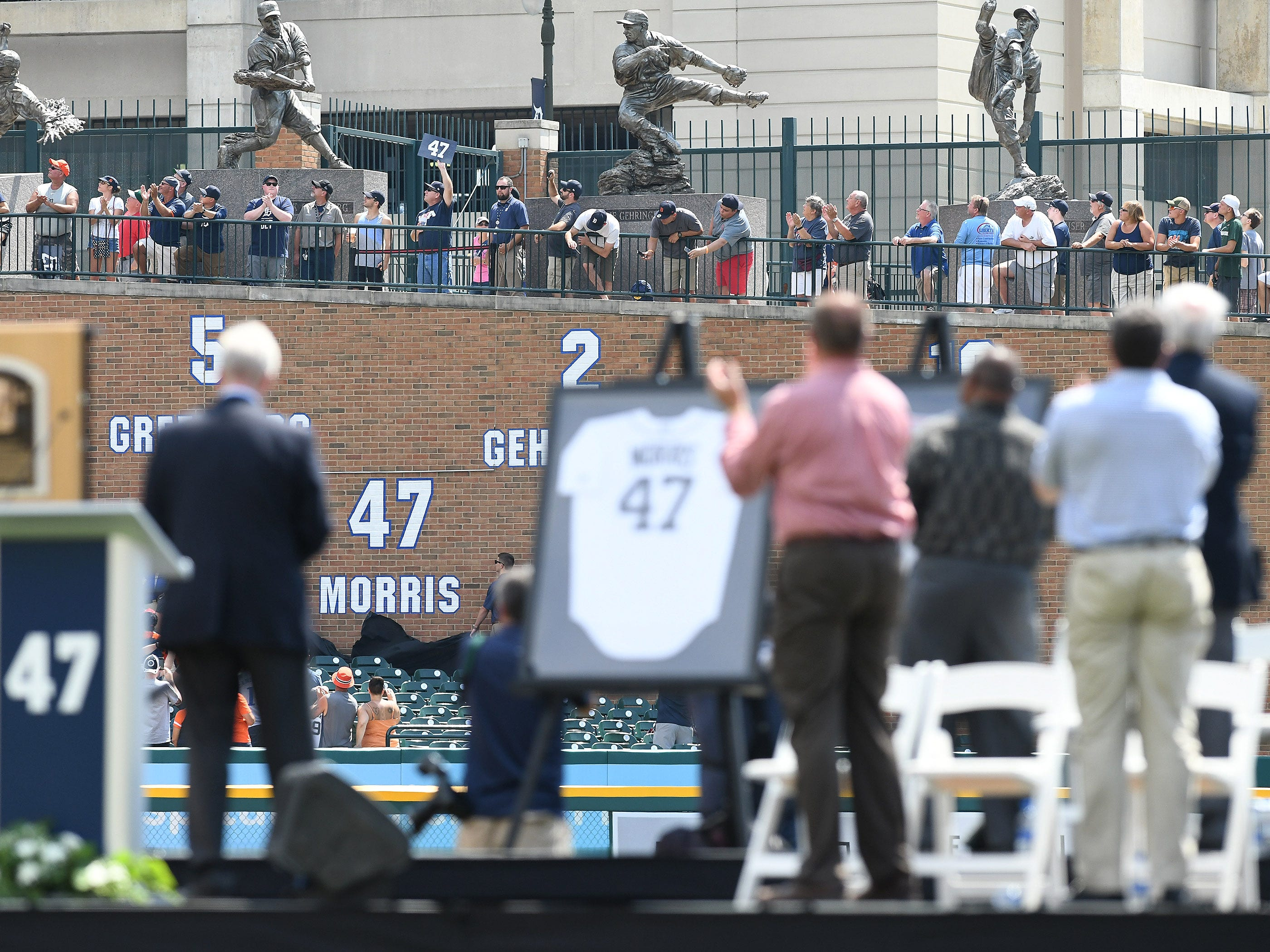 Fans and players on the stage stand and cheer as the #47 is uncovered on the center field wall during the special pregame ceremony to retire the #47 of Tigers pitcher and Hall of Fame pitcher Jack Morris.