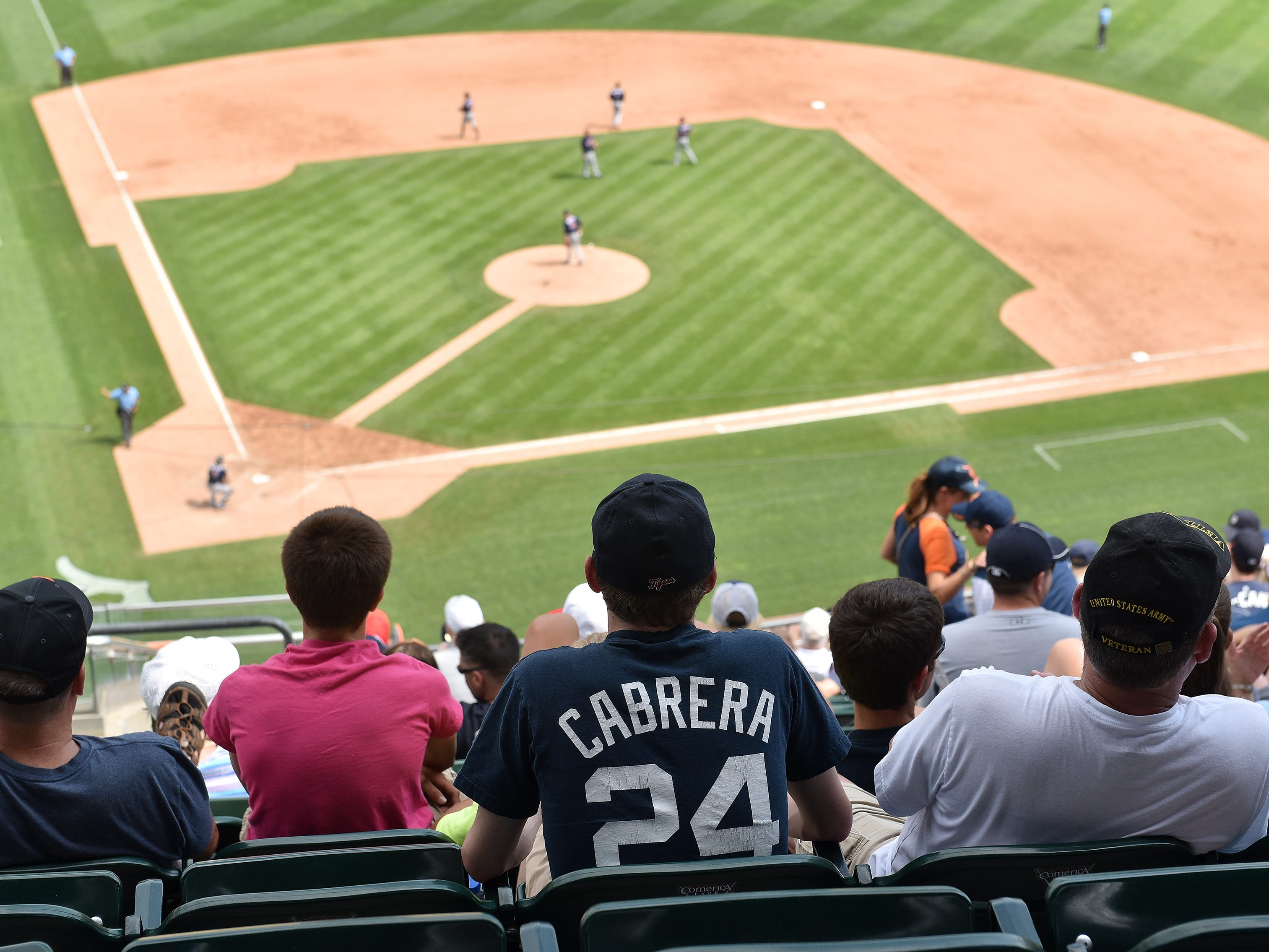 A fan with a Miguel Cabrera shirt sitting up in the shade of the upper deck.
