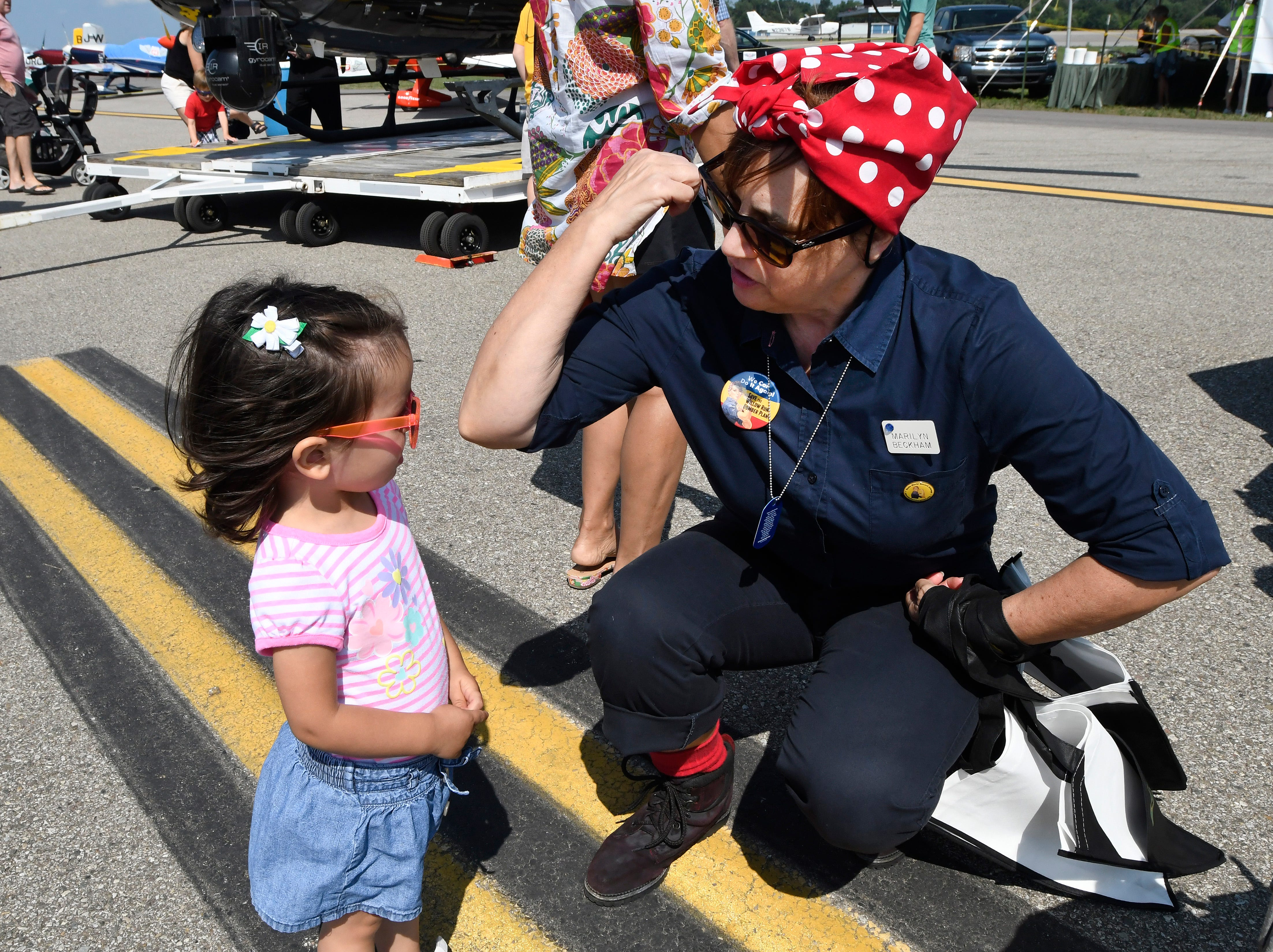 Volunteer Marilyn Beckham, dressed as Rosie the Riveter, flexes her muscle at a young girl who was too shy to show her muscles during the Air Show & Open House.