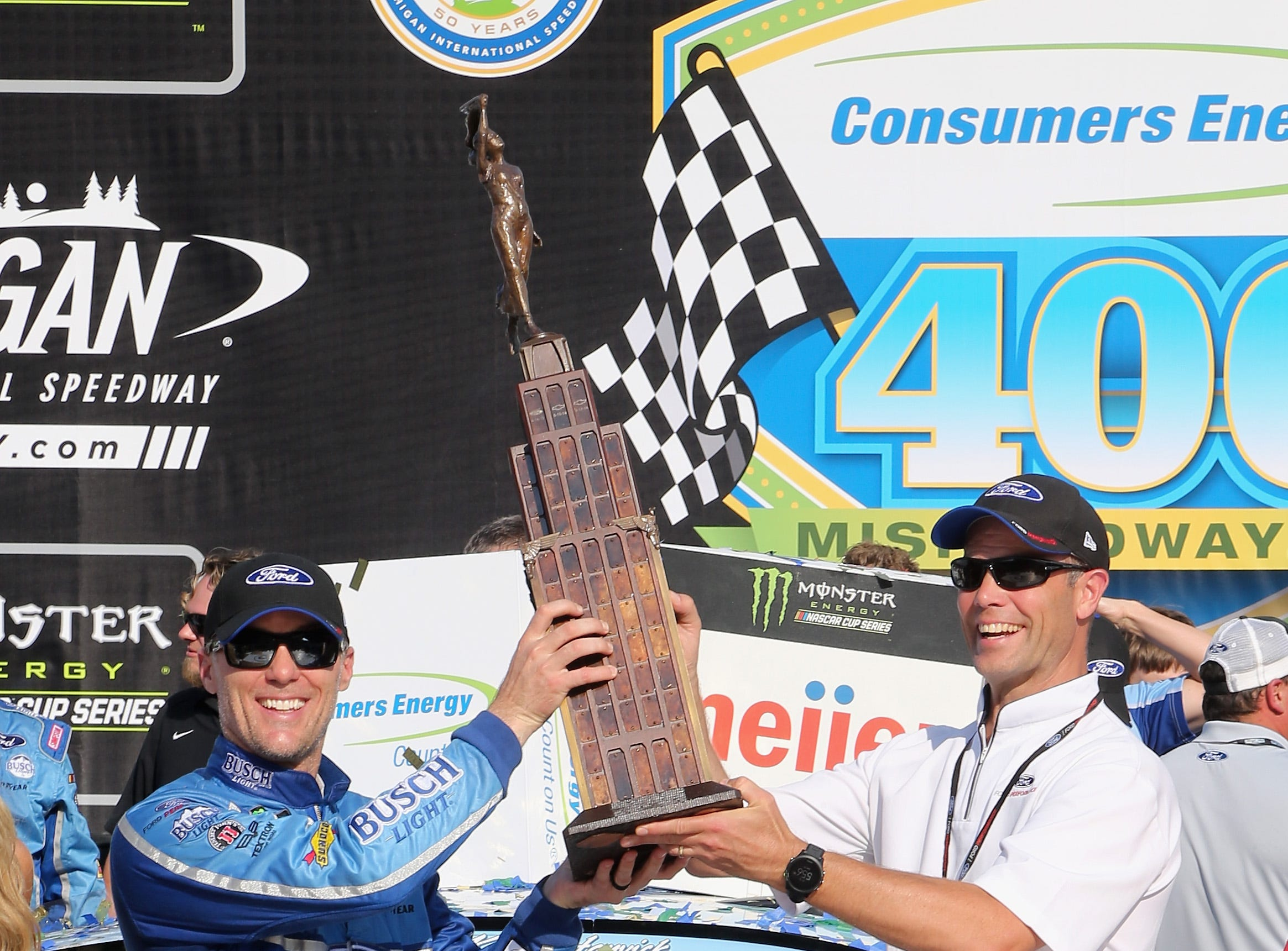 Kevin Harvick, driver of the #4 Busch Light/Mobil 1 Ford, celebrates with the trophy in Victory Lane after winning the Monster Energy NASCAR Cup Series Consmers Energy 400 at Michigan International Speedway.