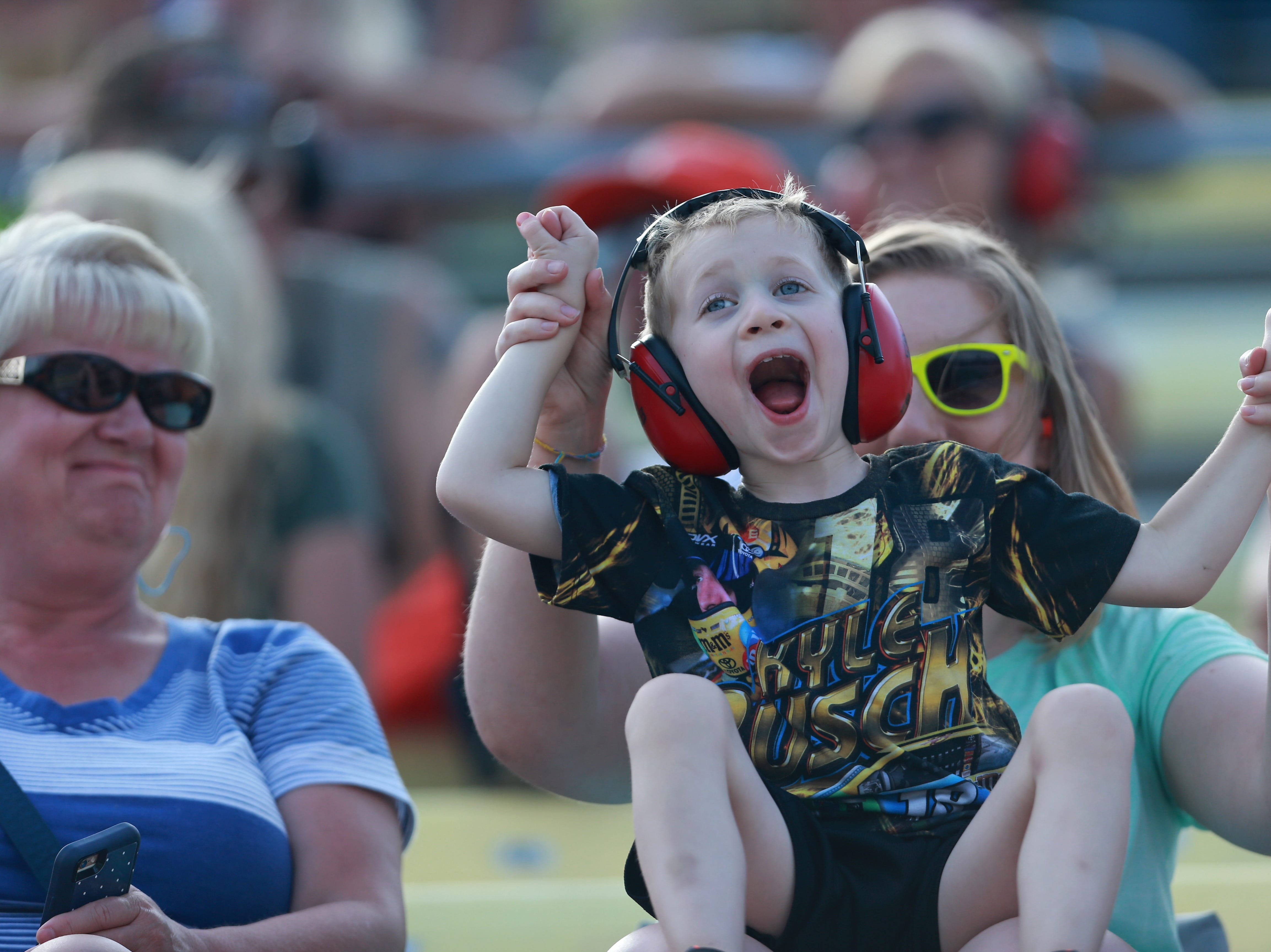 A young fan cheers during the Monster Energy NASCAR Cup Series Consmers Energy 400 at Michigan International Speedway.