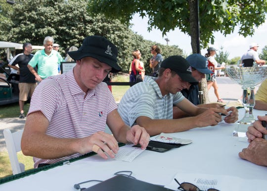 Stewie Hobgood, left, Matthew Ladd, middle, and Clinton Keown checks the score after completing the 2018 Courier and Press Men's City Golf Tournament on Sunday, August 12, 2018.