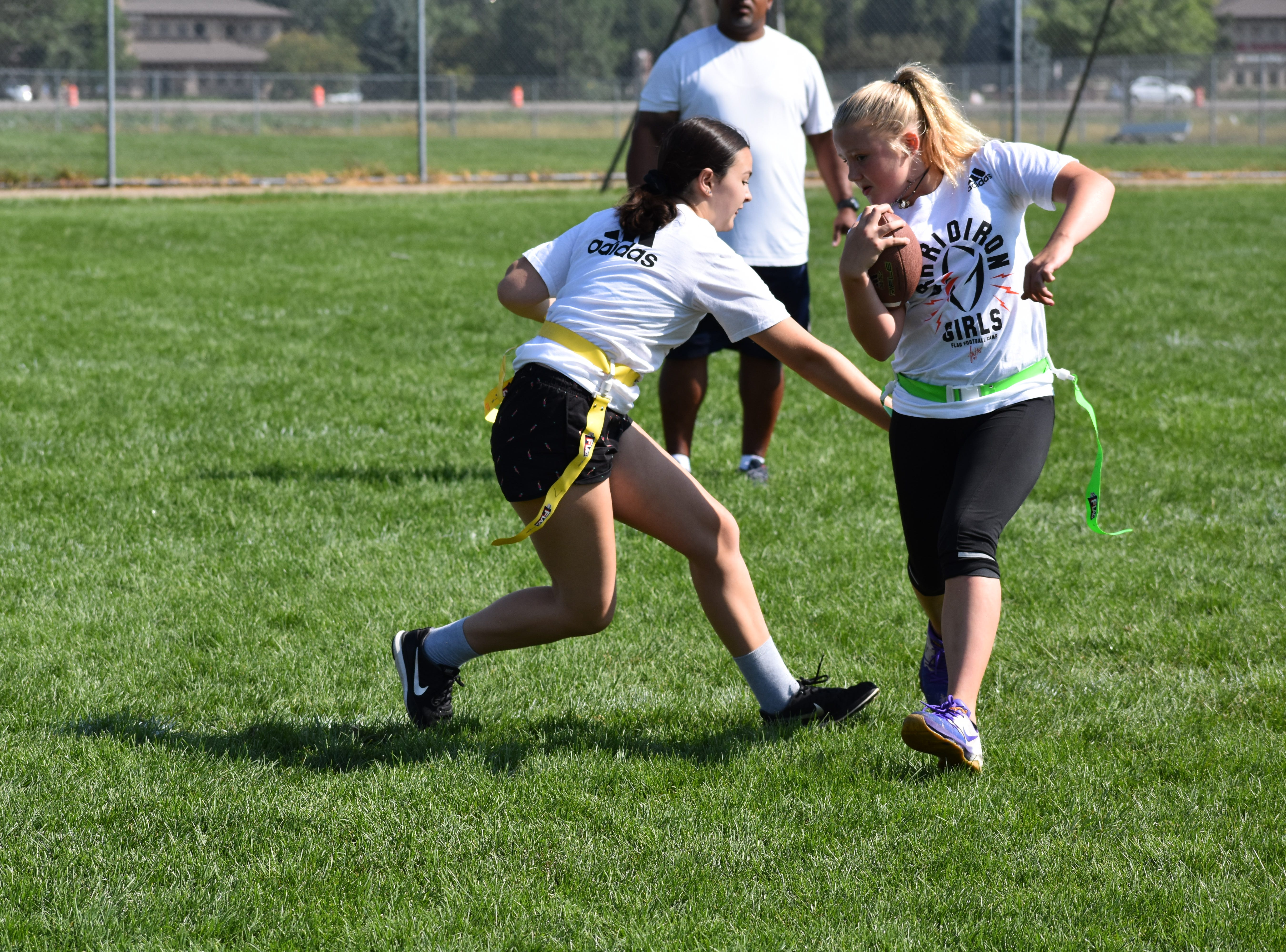 Jen Welter, the NFL's first female assistant coach, provides instruction Sunday at a Grrridiron Girls Flag Football Camp at Mountain View High School in Loveland. Anthony Stone, a high school football coach in Illinois, and players and coaches from the Denver Blaze women's football team helped run the camp.