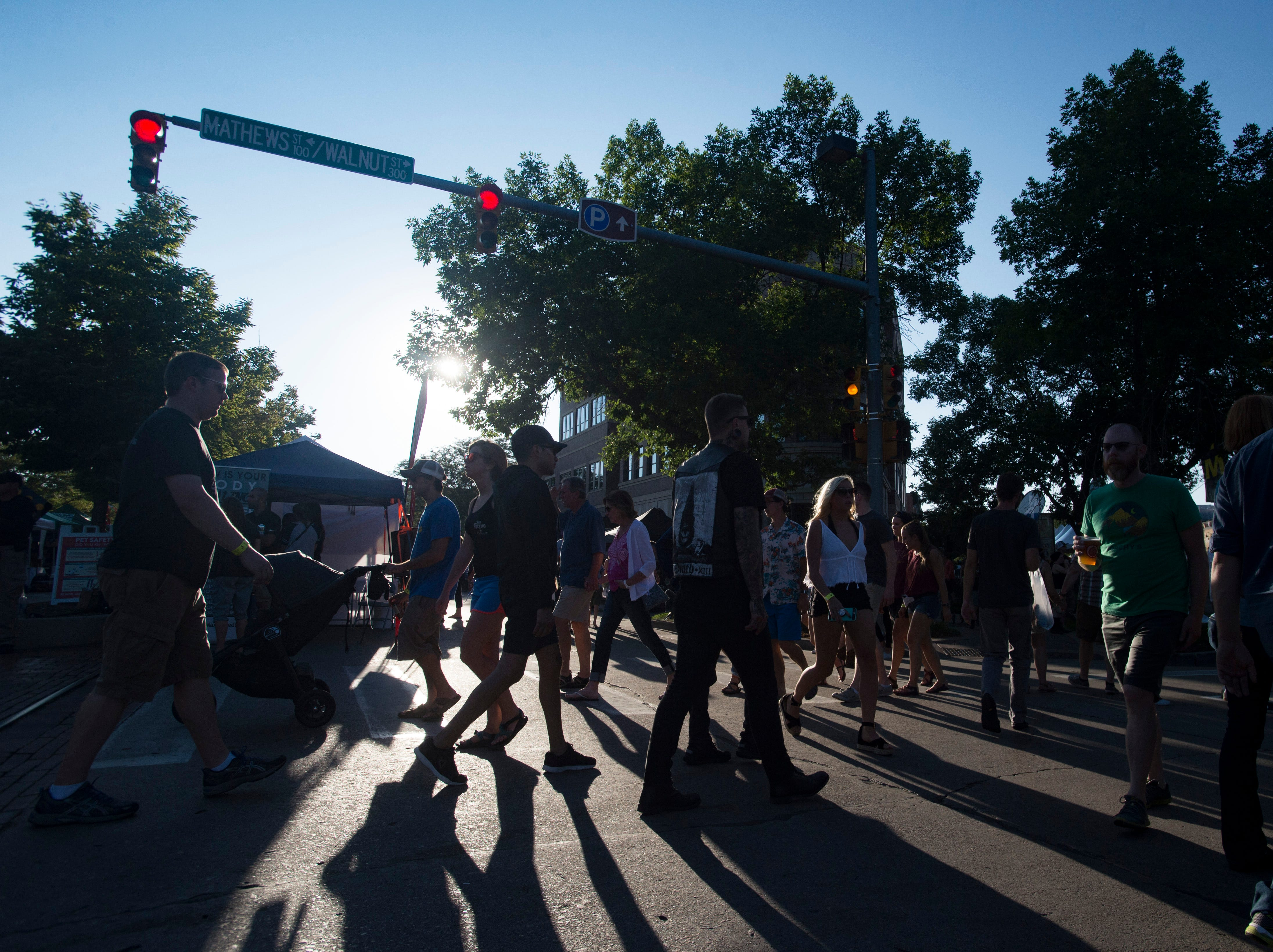 People cast shadows as they cross Mountain Avenue during Bohemian Nights at NewWestFest in Old Town on Saturday, August 11, 2018.