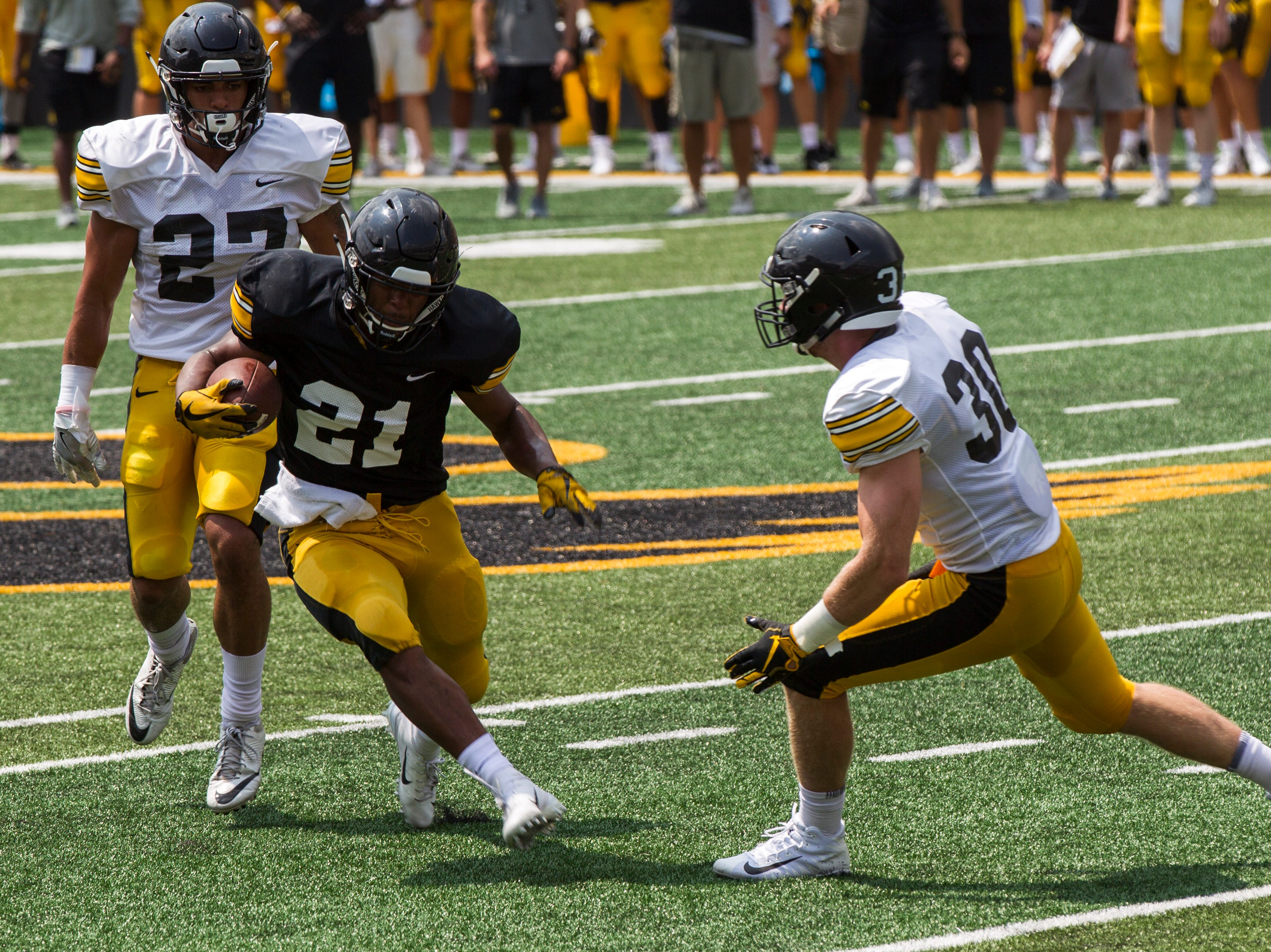 Iowa running back Ivory Kelly-Martin (21) rushes while getting covered by Amani Hooker (27) and Jake Gervase (30) during a Kids Day practice on Saturday, Aug. 11, 2018, at Kinnick Stadium in Iowa City.