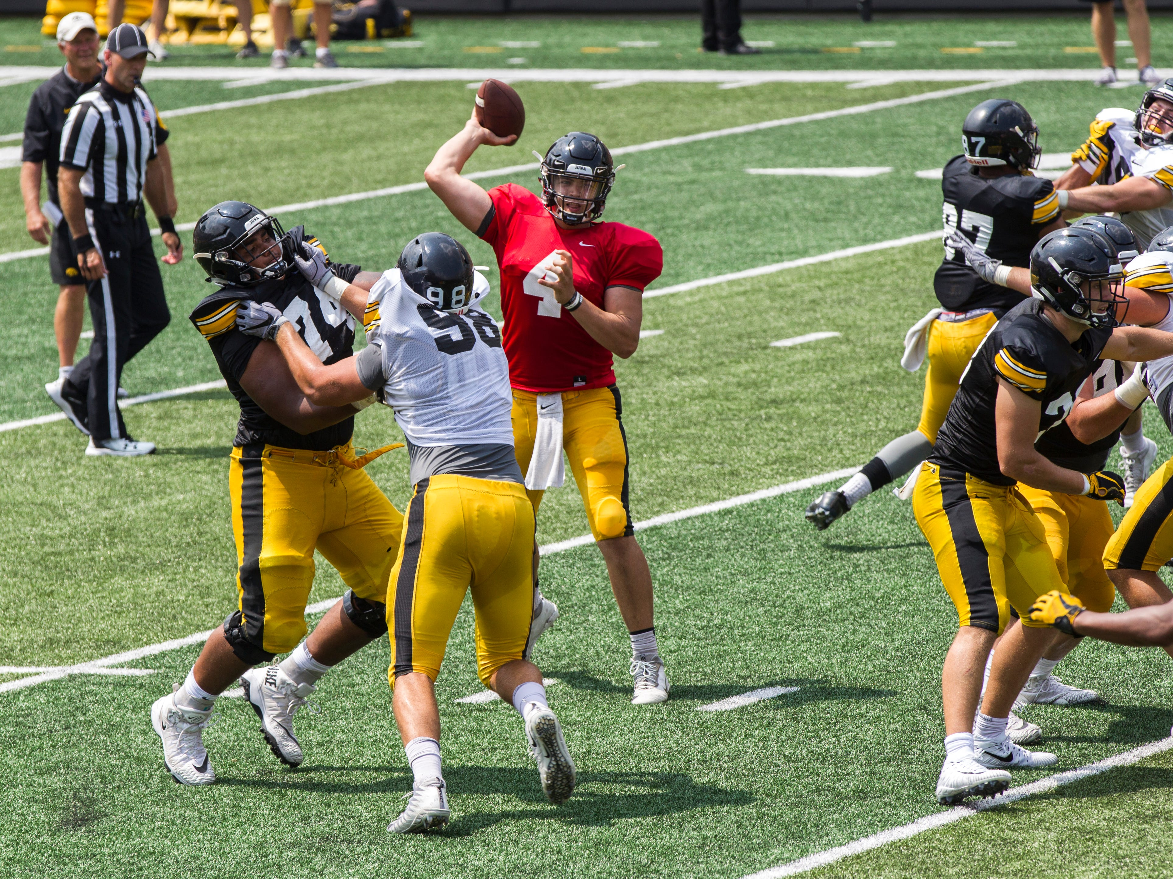 Iowa quarterback Nate Stanley (4) looks to pass while offensive lineman Tristan Wirfs (74) gets a block against Anthony Nelson (98) during a Kids Day practice on Saturday, Aug. 11, 2018, at Kinnick Stadium in Iowa City.