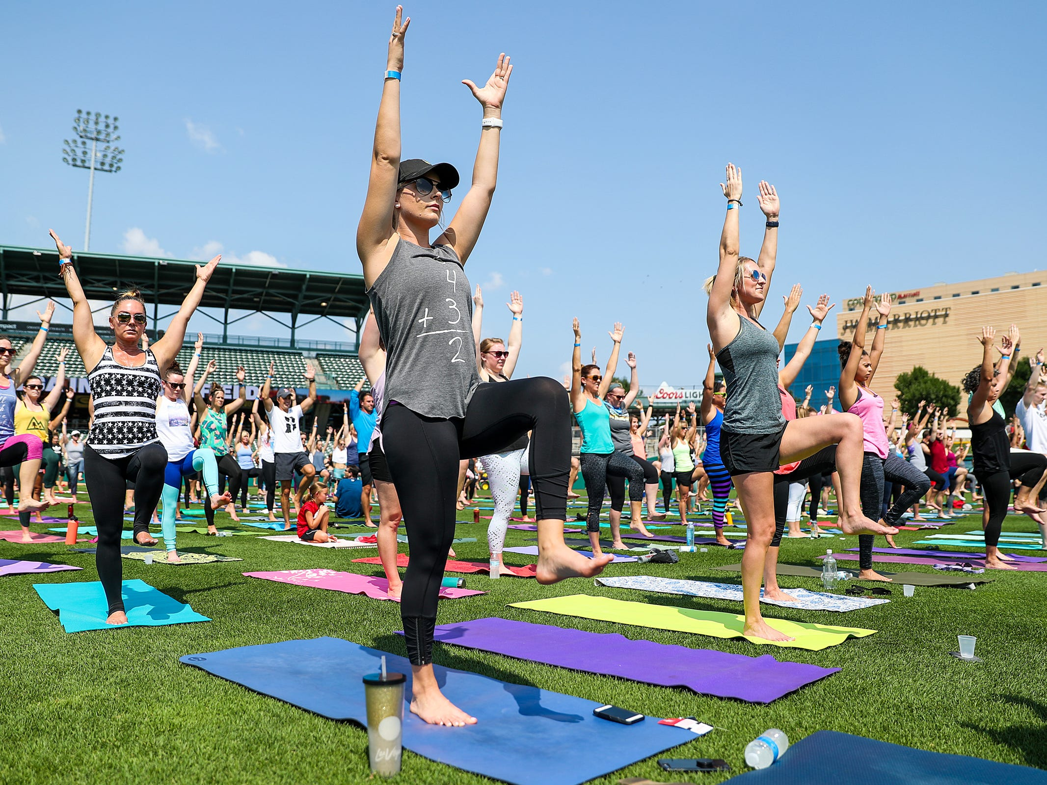 Yogis practice vinyasa flow during Yoga in the Outfield at Victory Field in Indianapolis, Sunday, Aug. 12, 2018.