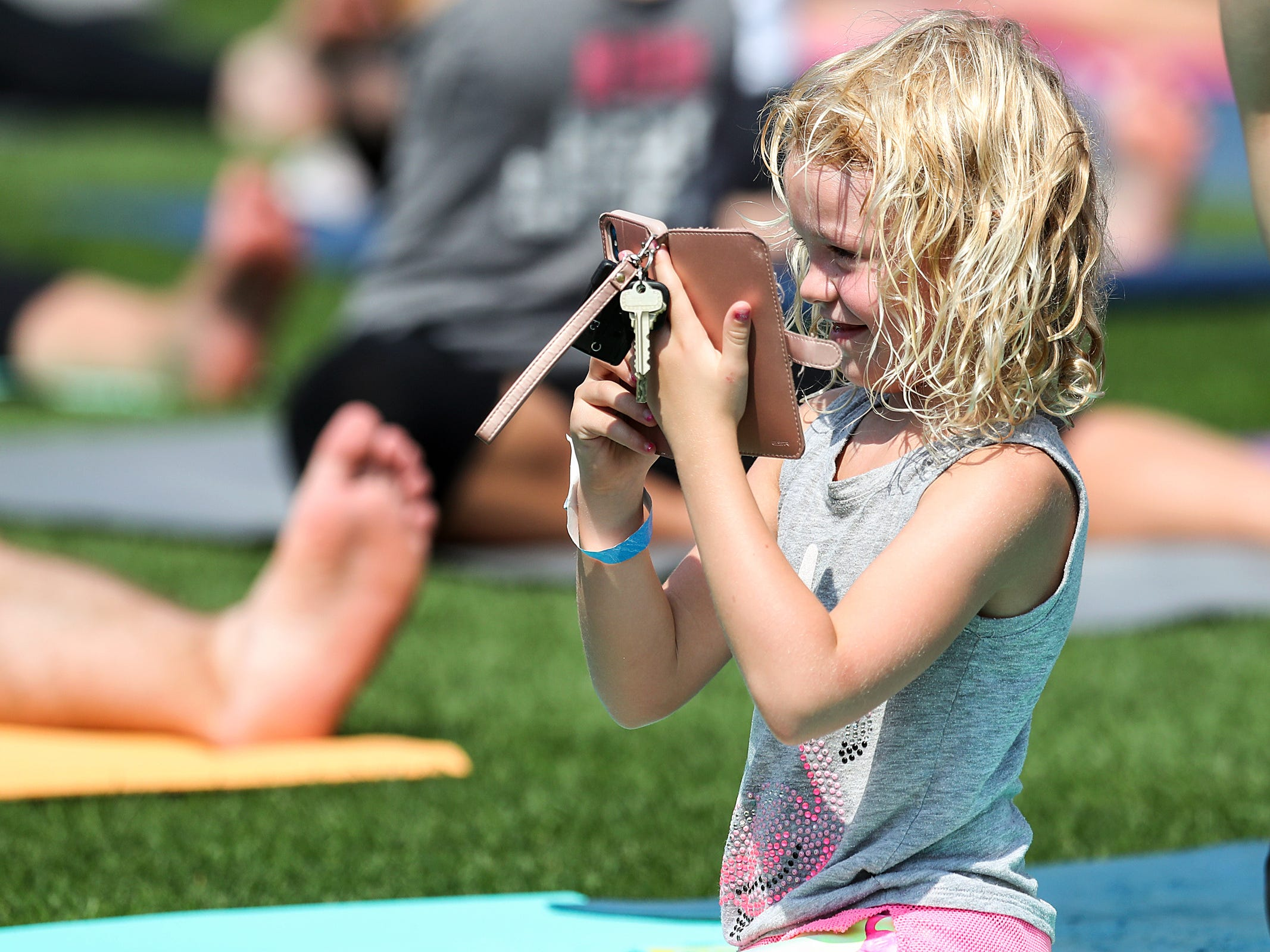 A young one takes photos as yogis practice vinyasa flow during Yoga in the Outfield at Victory Field in Indianapolis, Sunday, Aug. 12, 2018.