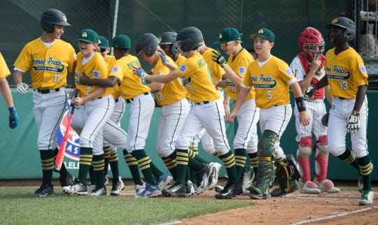 The Michigan squad, en route to their 13-0 victory over Indiana, celebrates one of their two home runs, Grand Park, Westfield, Saturday, Aug. 11, 2018. The Grosse Pointe squad will represent the Great Lakes region in the upcoming Little League World Series.