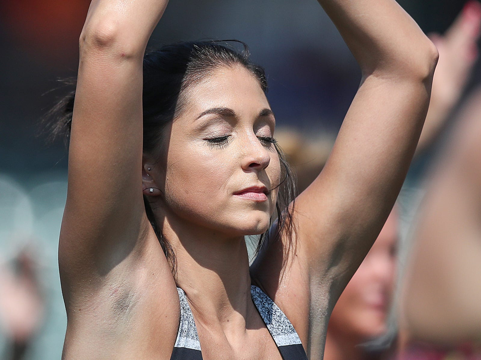 Alanna Martella, an anchor for RTV6, practices yoga at Yoga in the Outfield at Victory Field in Indianapolis, Sunday, Aug. 12, 2018.