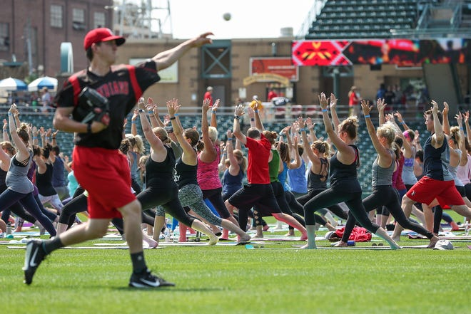 A few of the Indianapolis Indians warm up for their afternoon game while yogis practice vinyasa flow during Yoga in the Outfield at Victory Field in Indianapolis, Sunday, Aug. 12, 2018.