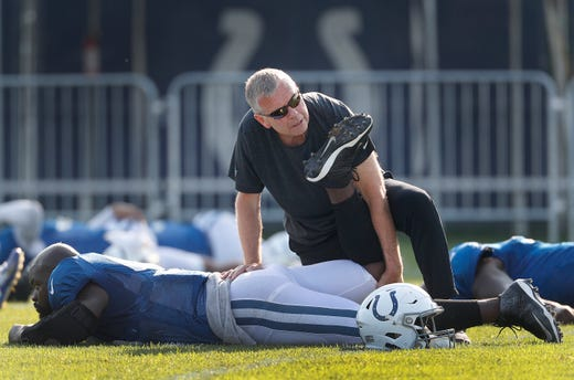 Indianapolis Colts director of sports performance Rusty Jones works on Anthony Johnson (96) during their preseason training camp at Grand Park in Westfield on Sunday, August 12, 2018.