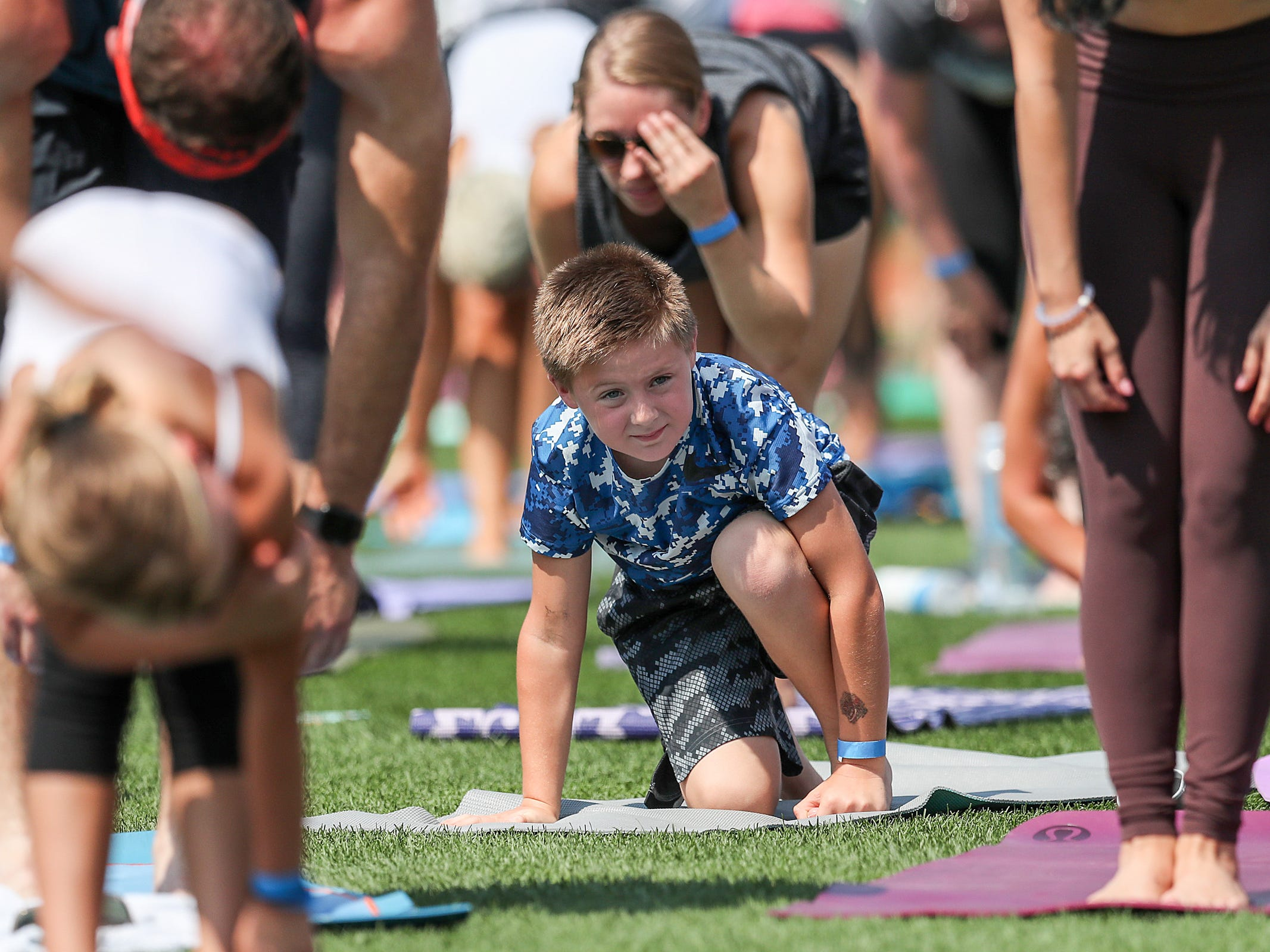 Kyle Carr, 7, of Detroit, pauses between poses during Yoga in the Outfield at Victory Field in Indianapolis, Sunday, Aug. 12, 2018.