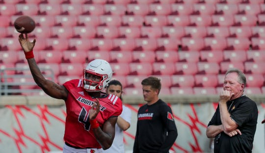 Louisville's Jawon Pass practices at fan day as coach Bobby Petrino looks on.
