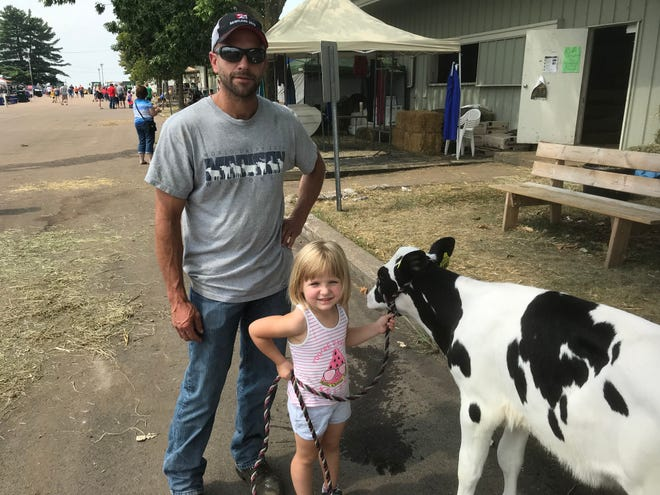 """Dairy farmer Brian Begert and his daughter Abigail at the Clark County Fair in Neillsville Saturday. Begert said of the tariffs that are affecting farmers like him, 'I hope they can get something resolved and it ends up being better in the long run. ... I just hope that it works out."""""""
